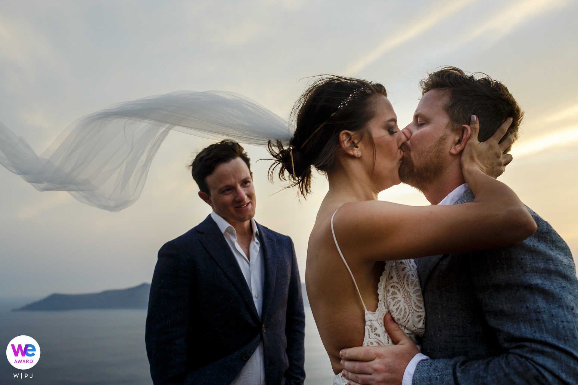 Fira, Santorini, Greece Elopement Photo Images | The veil and hair of the bride were flying about in the hot breeze and there were teardrops