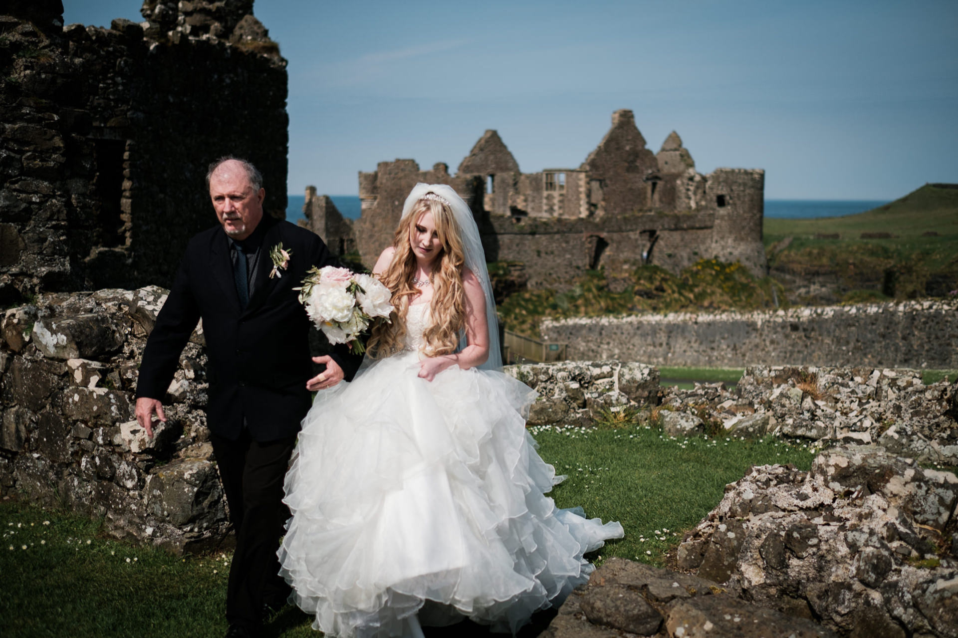 Dunluce Castle, Northern Ireland Elopement Couple Image | the bride and her father make their way through the ruins of the castle