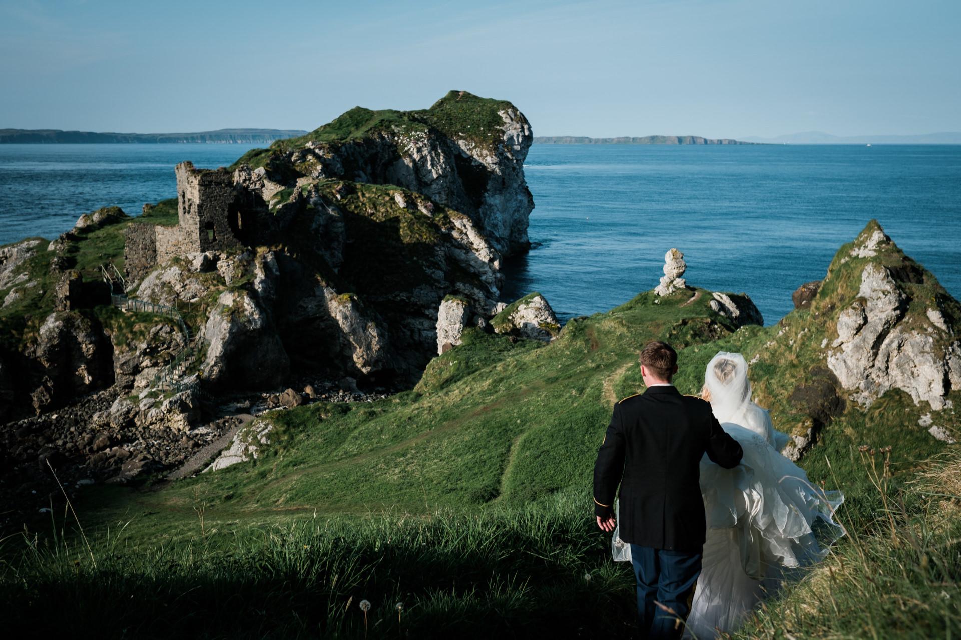 Castle Elopement Photography in Noord-Ierland | Het paar loopt na hun ceremonie in het nabijgelegen Dunluce Castle