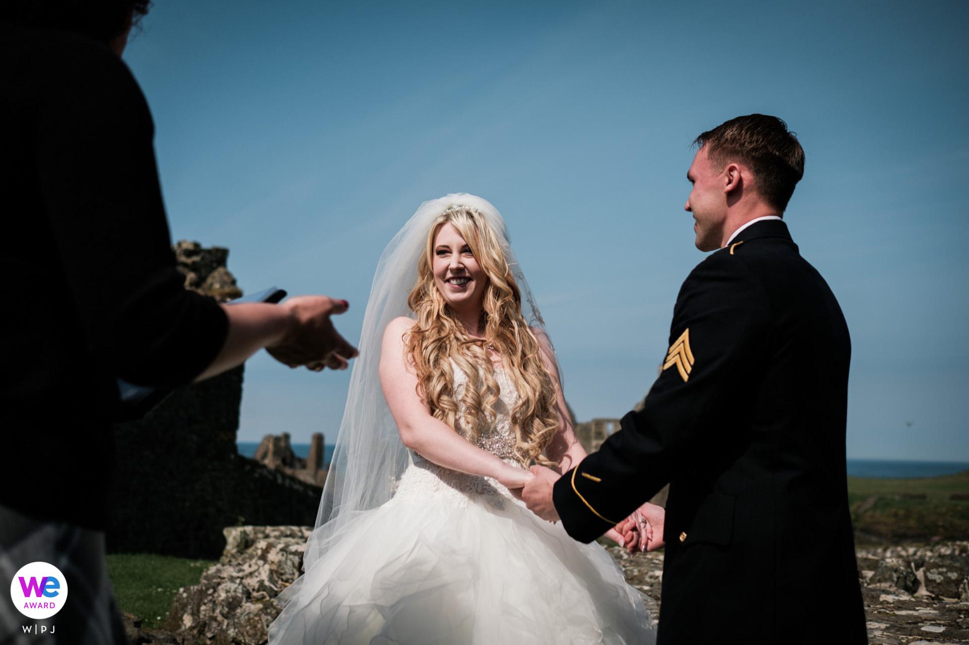 Dunluce Castle, Noord-Ierland Elopement Fotograaf | De bruid en bruidegom luisteren naar de woorden van hun celebrant