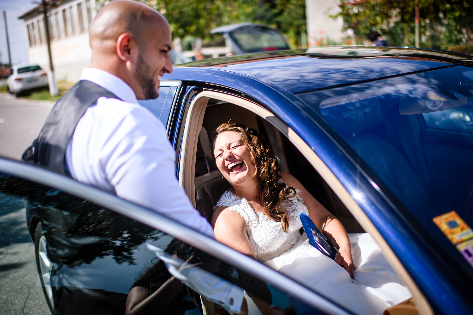 Bulgaria Elopement Picture | The groom helps the bride into a car