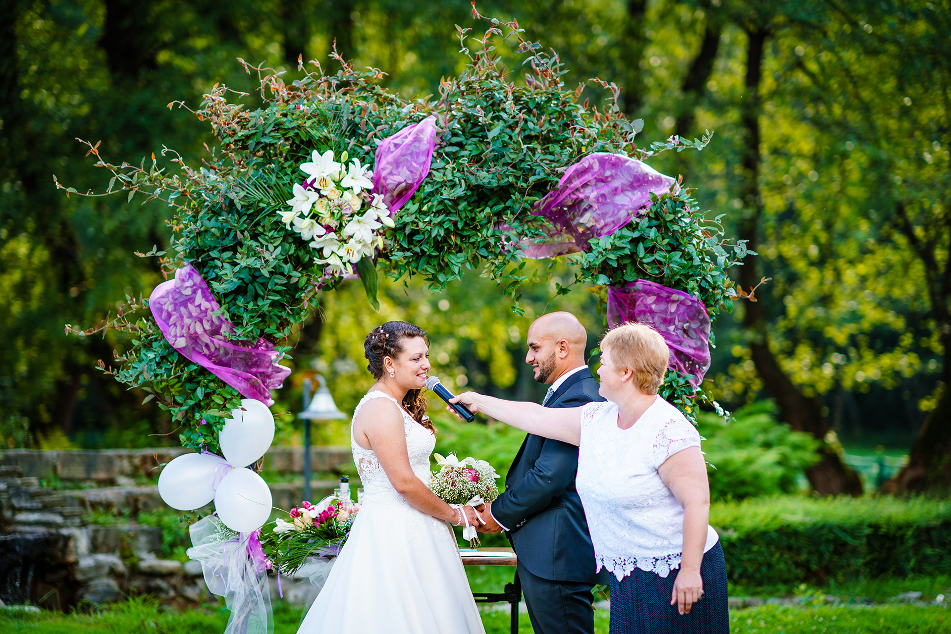 Outdoor Ceremony Image from a Bulgaria Elopement | Standing beneath a floral arch, the bride's big moment has arrived