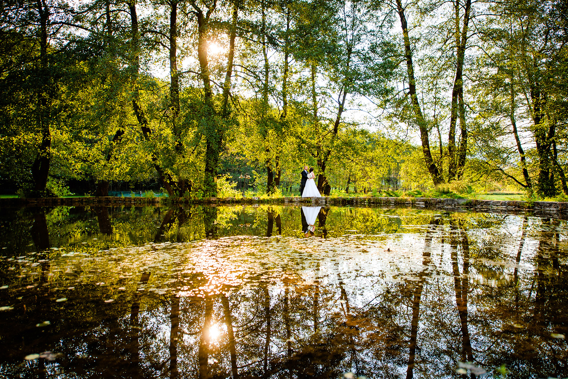 Bulgaria Elopement Portrait Photographer | the newlyweds take a private minute to themselves to walk together along the edge of a pond,