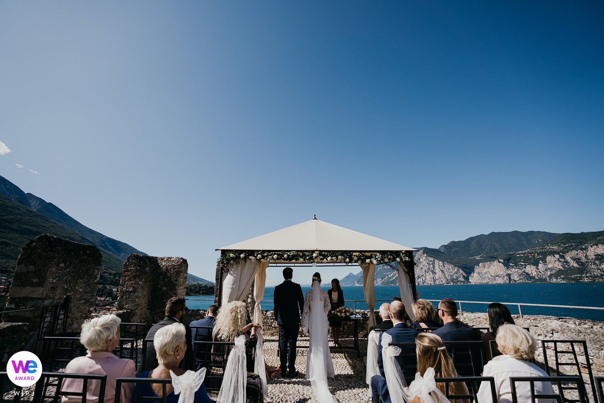 Malcesine Castle, Italy Elopement Photography | The wonderful view of the wedding ceremony, a few guests, and the lake