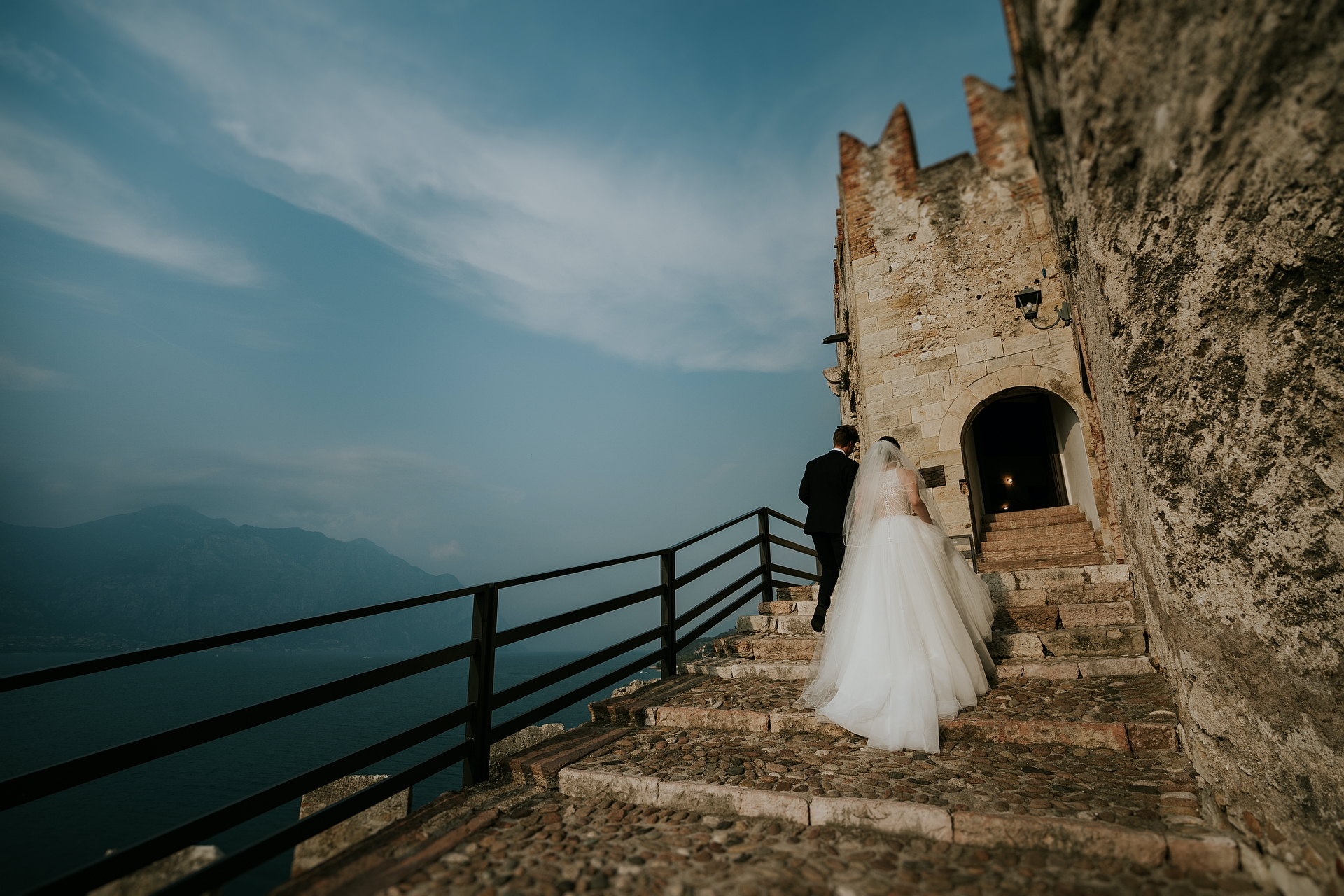 Scaliger Castle - Italy Elopement Photographer | the bride and groom climb the last staircase before crossing the ancient gate of the castle