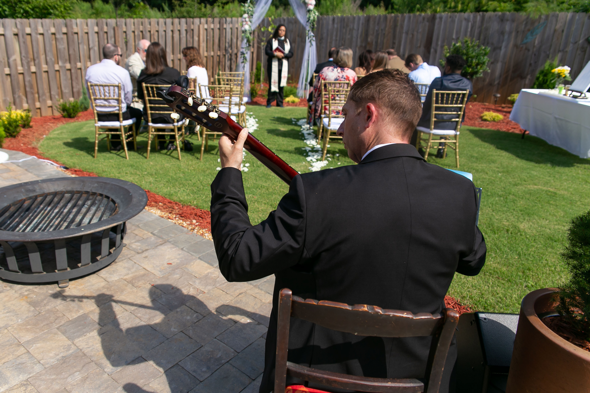 Backyard Elopement Ceremony Picture | A classical guitarist plays for guests
