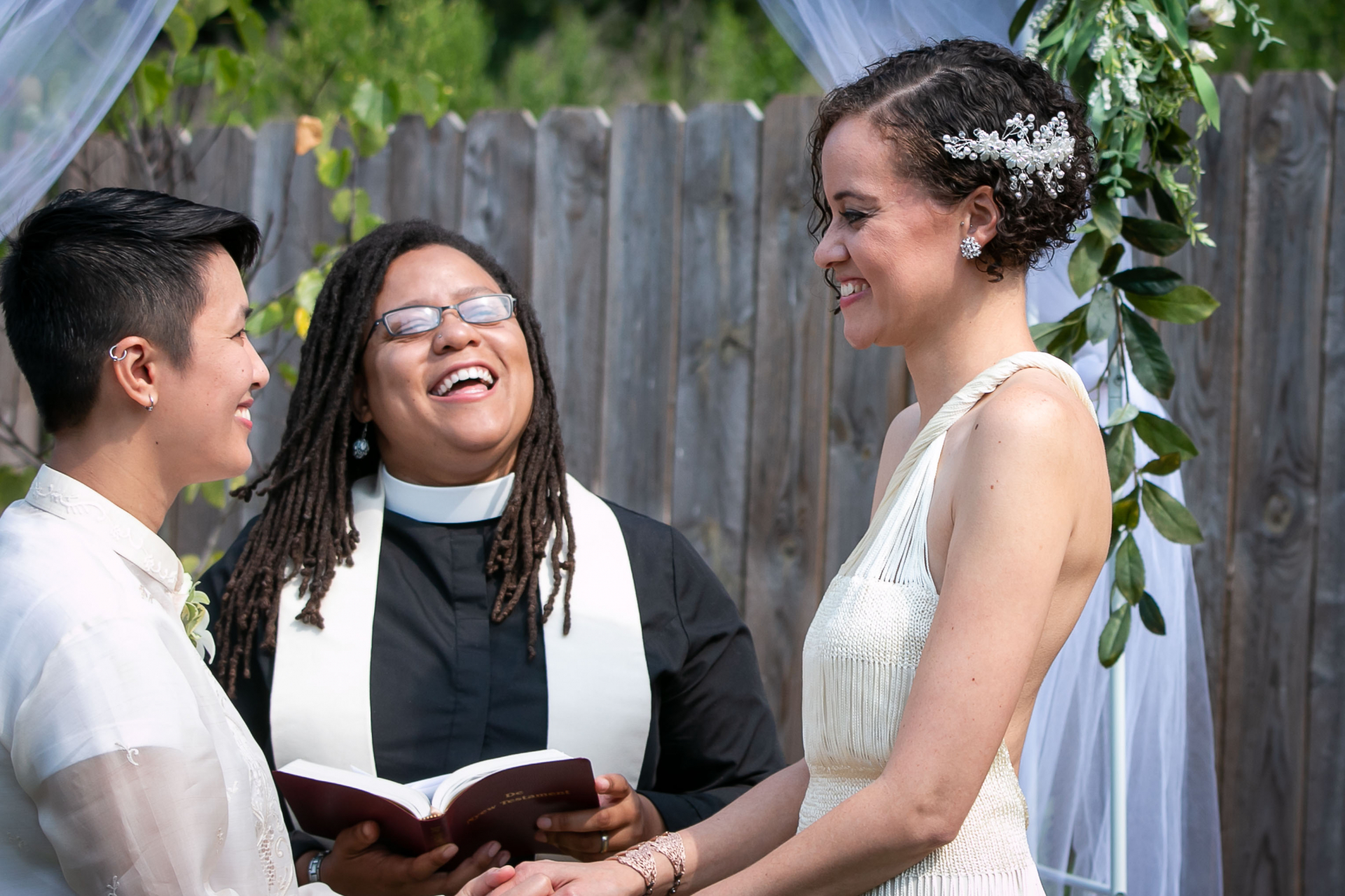 Outdoor At-Home Elopement Ceremony Image | The couple laughs together with their priest during the ceremony