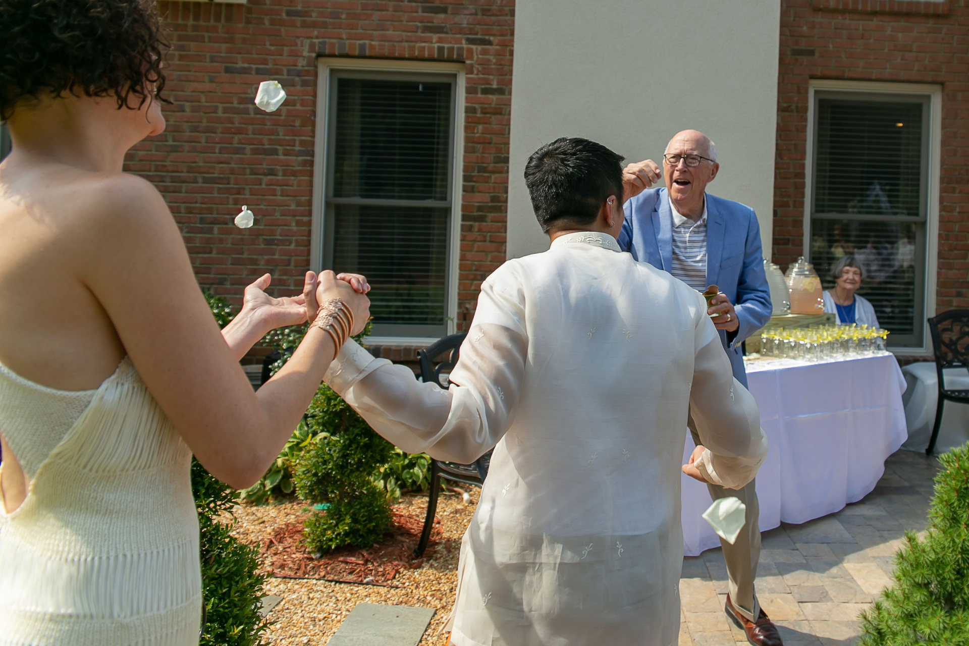 Backyard Elopement Celebration Images | grandfather throws flower petals on the couple as they leave their ceremony