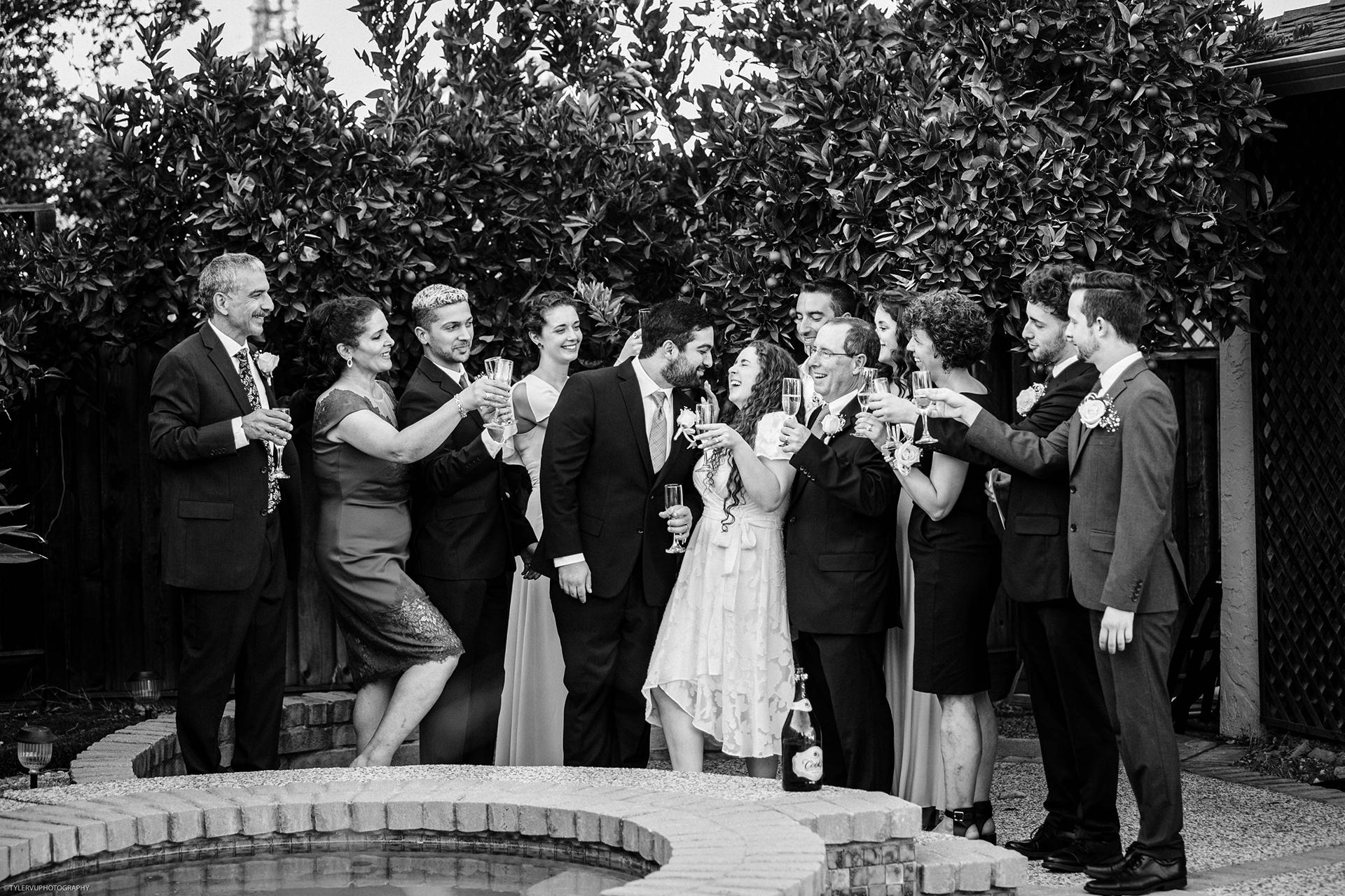 California Backyard Elopement Reception Toast Photo | Still enjoying the beautiful sunshine, guests gather around the couple