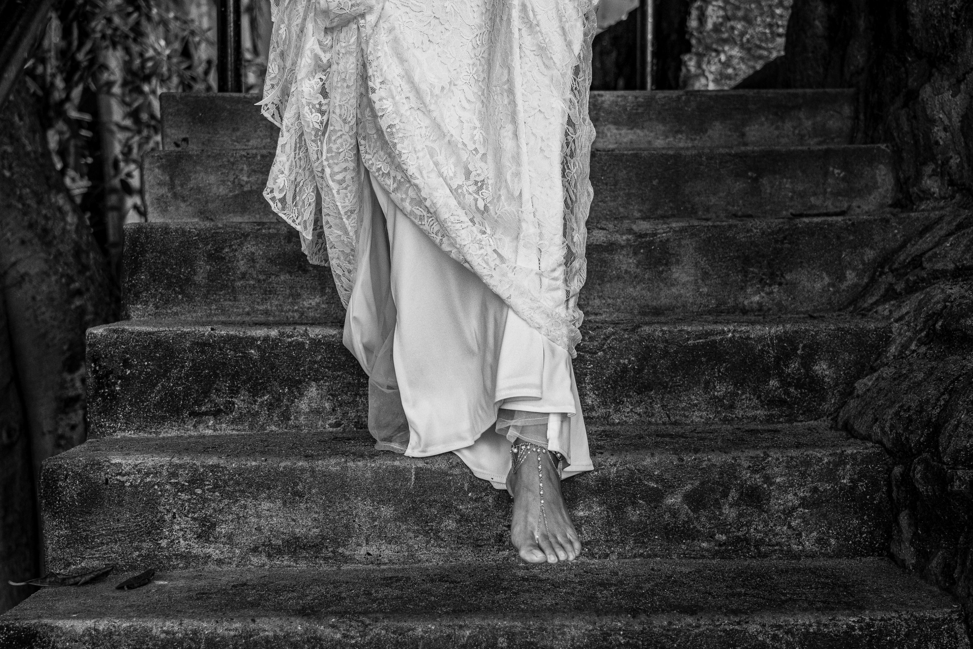 Conchas Chinas Beach, Mexico Elopement Dress Detail Image | The bride holds up her lace dress as she walks barefoot down a flight of rustic, stone stairs