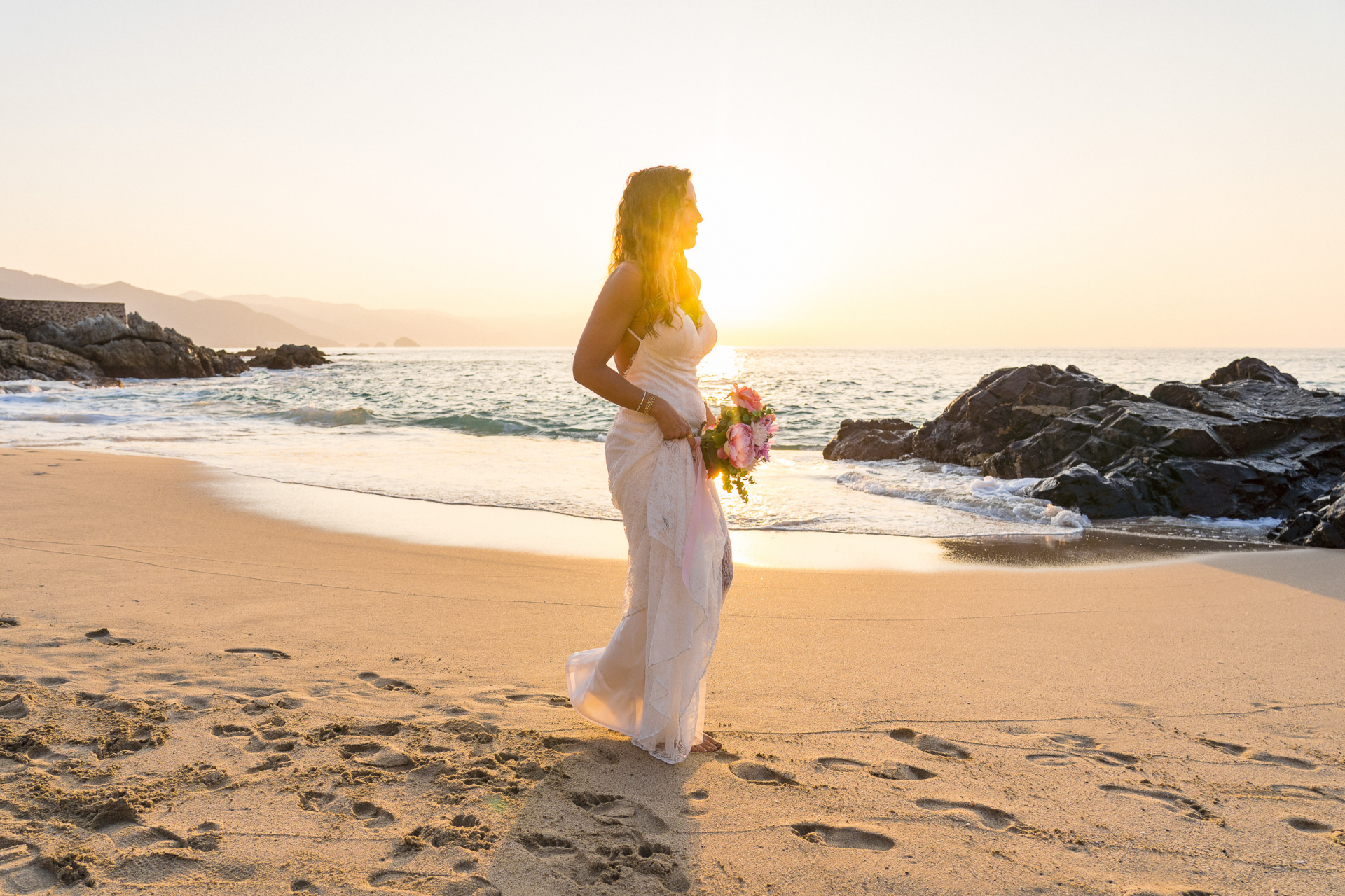 Puerto Vallarta Beach Elopement Bridal Image | The bride, surrounded by sunlight and waves crashing on rocks, walks along the beach