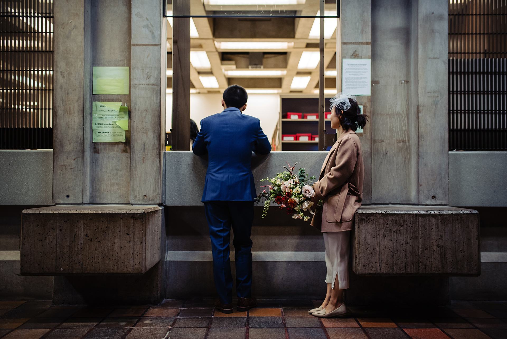 Images of a Boston City Hall Wedding Elopement   The bride-to-be looks on, holding her bouquet of flowers