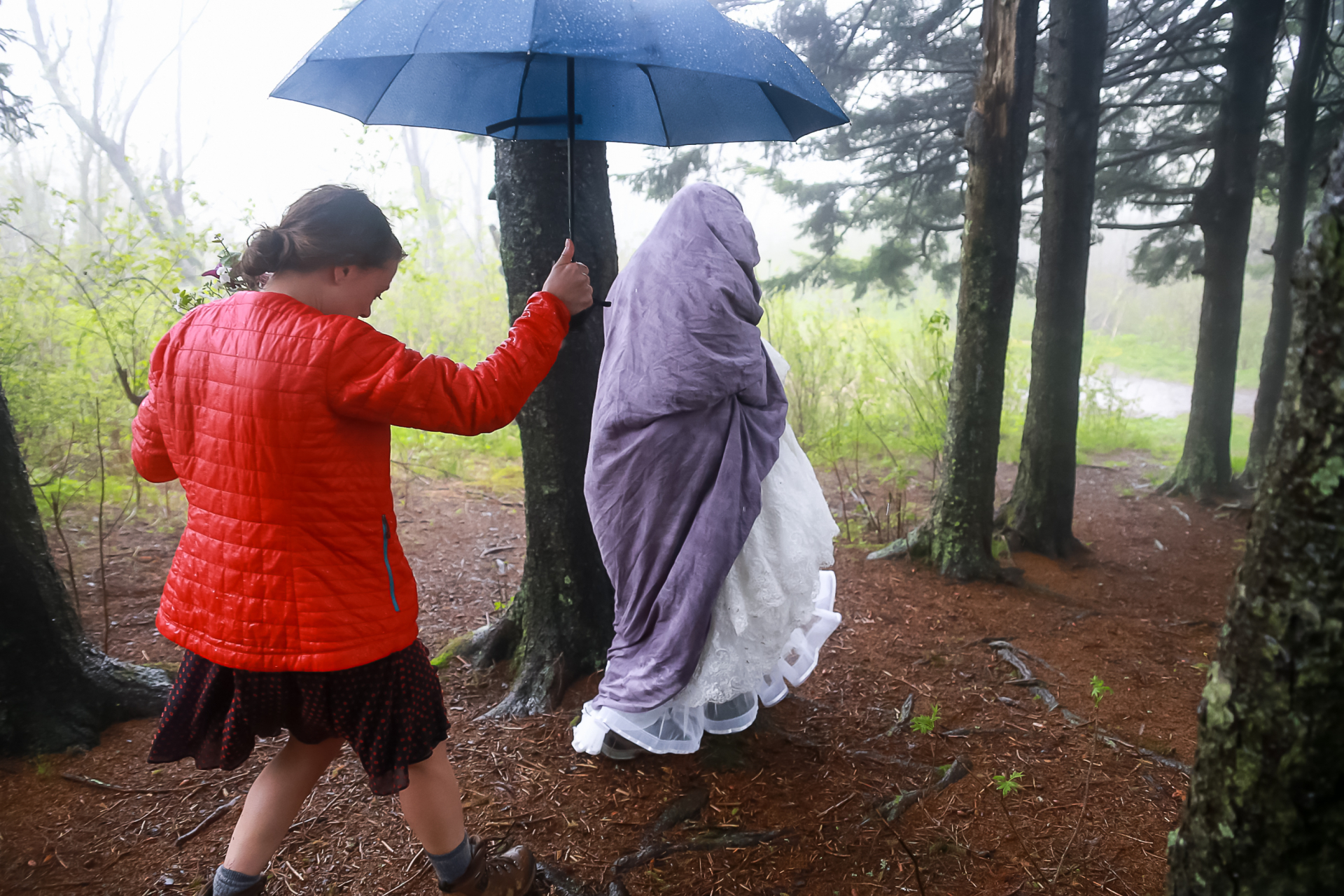 North Carolina Outdoor Elopement Photo | The maid of honor helps the bride stay dry from the rain before her wedding ceremony
