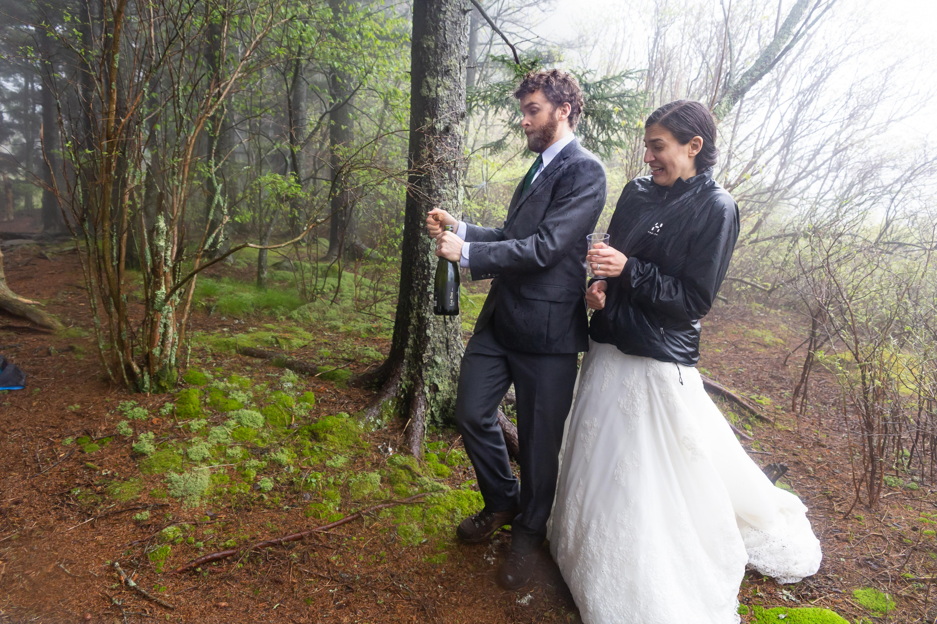 North Carolina Elopement Photo from the Forest Ceremony | The groom pops open a bottle of champagne