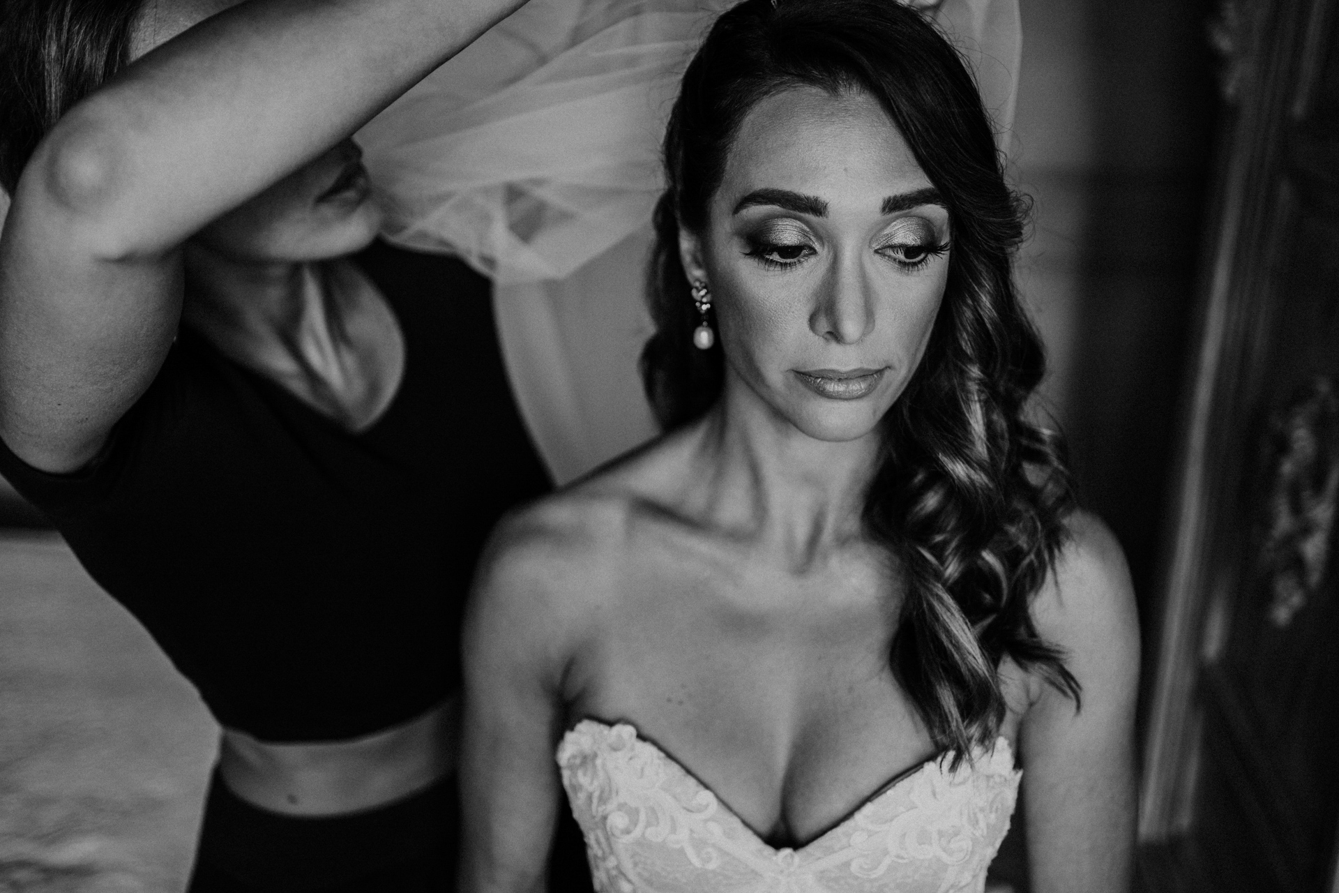 Tuscan Hills, Italy Elopement Photos | The bride wears a veil helped by the make up artist - MUA