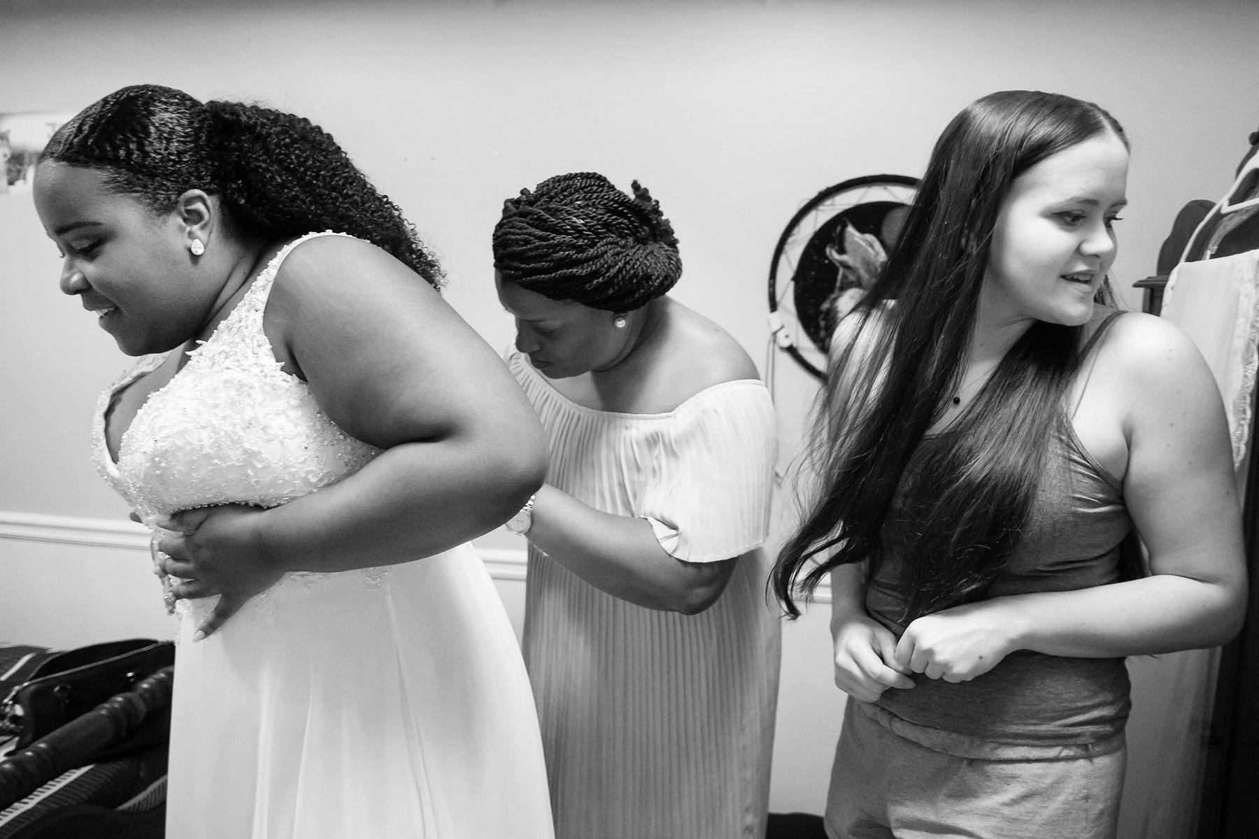 Backyard Wedding Photos - WPJA | Mom helps her daughter into her wedding dress