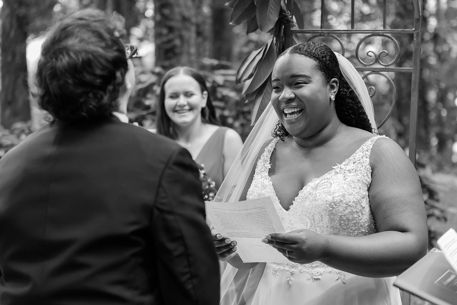 Small Backyard Wedding Photography | maid of honor laugh while reading the vows