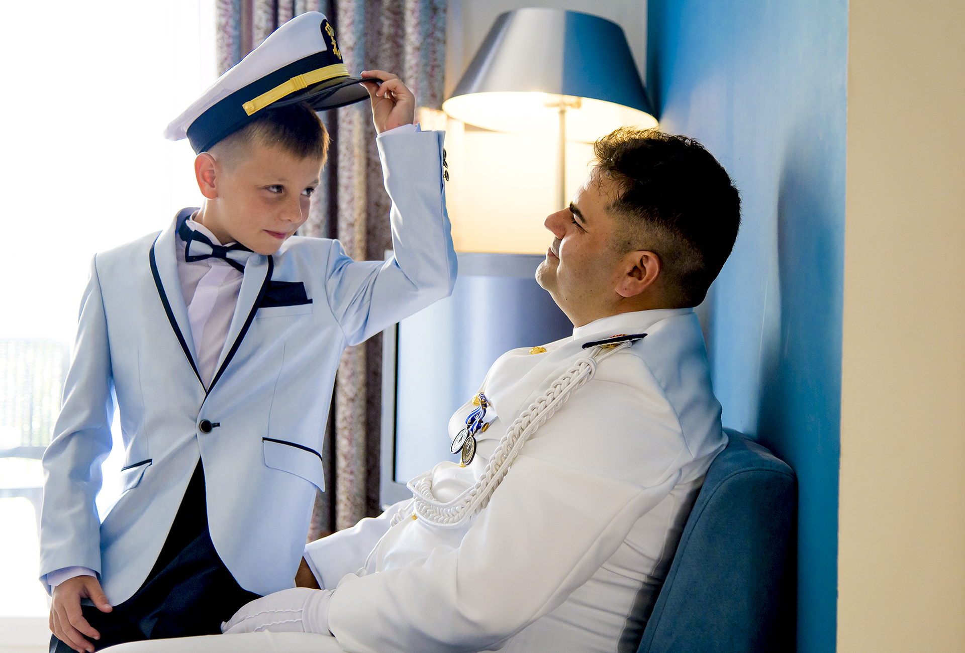 Aguilas, Spain Military Elopement Image | Sharing his military cap with his son, the groom took a moment to connect with the boy