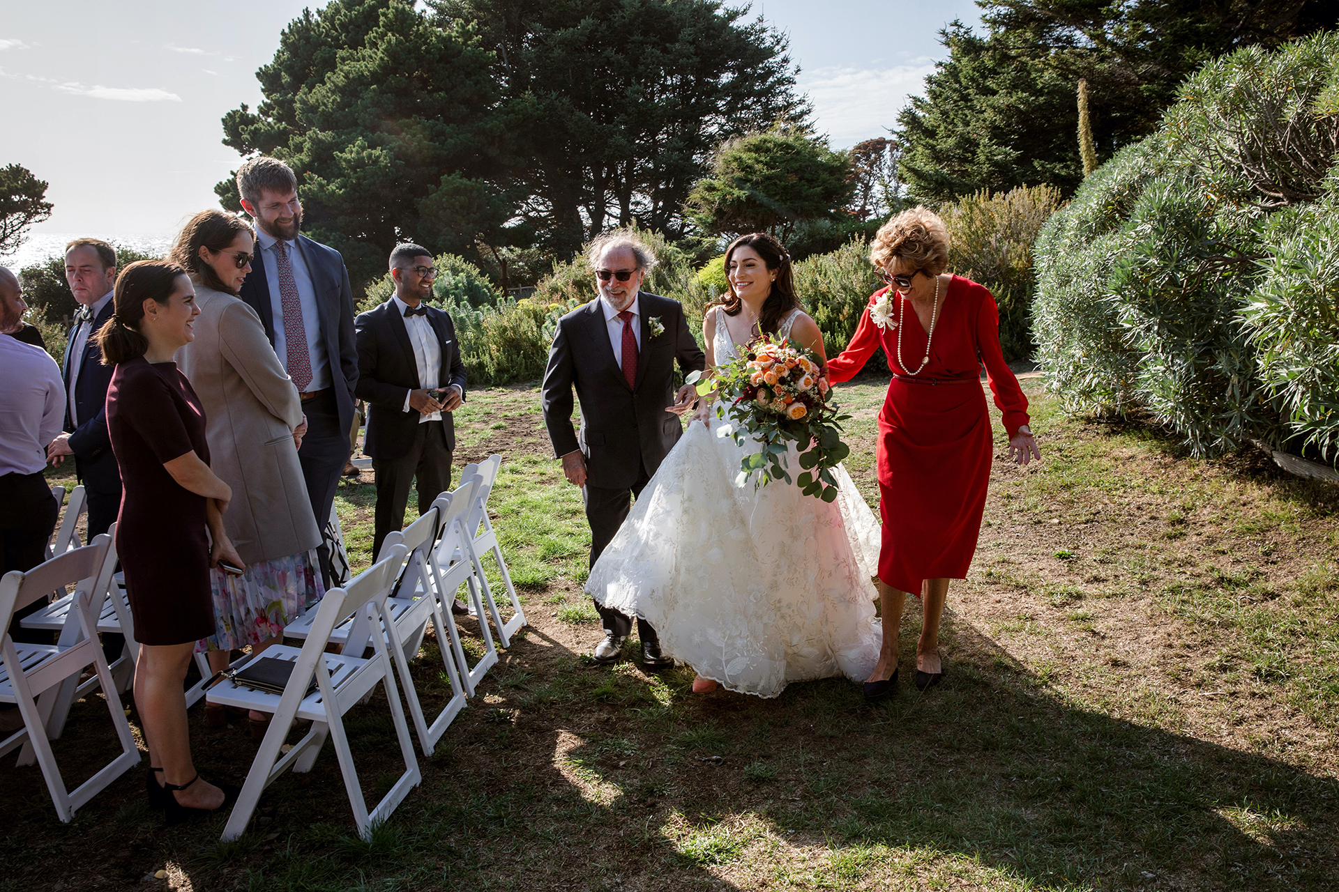 Heritage House, Mendocino Outdoor Elopement Image   The bride has a big smile as her mom and dad walk with her