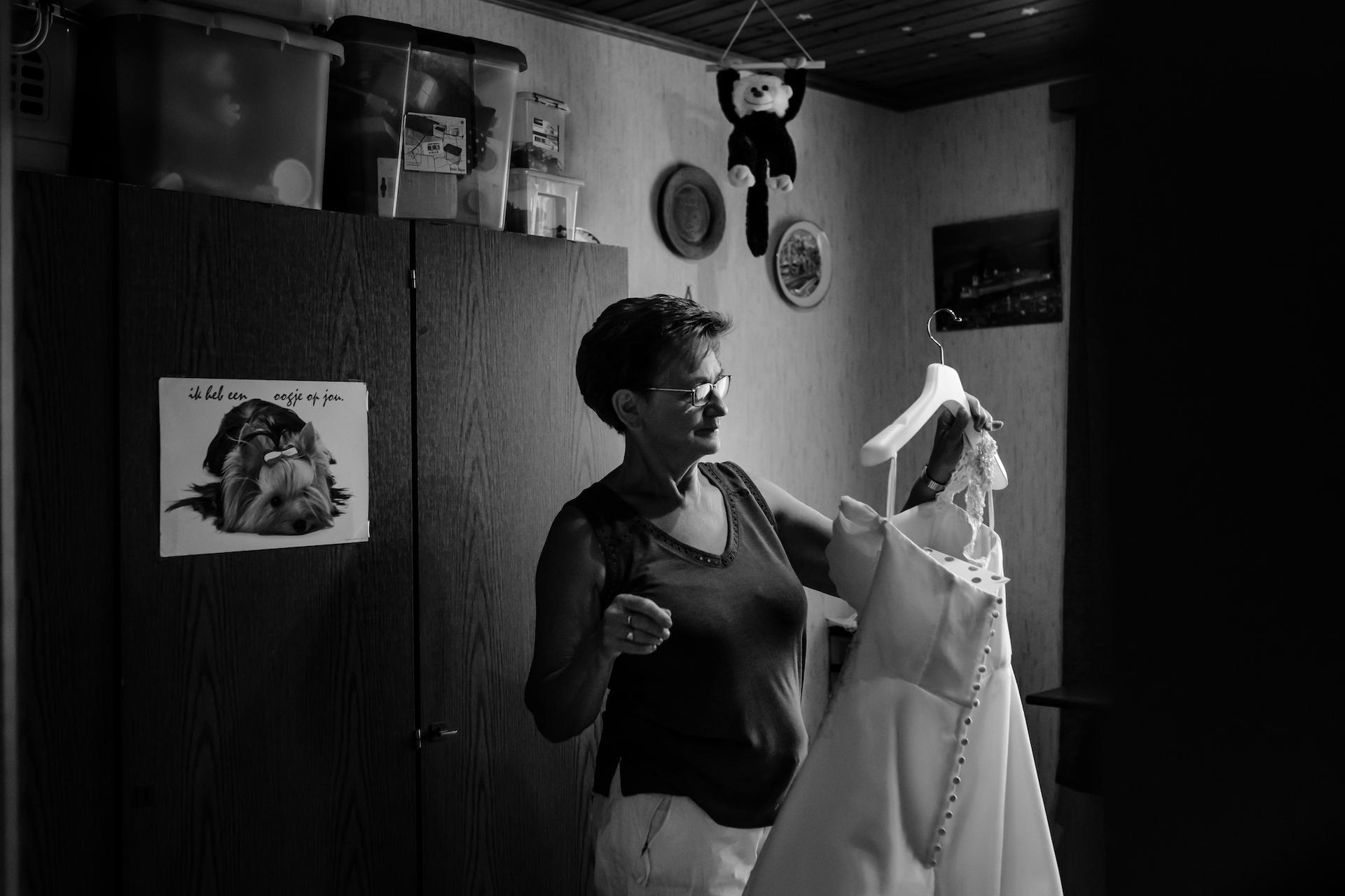 Sint-Truiden, Brussels, Belgium Elopement Photo at Home | The bride's mother retrieves the wedding dress