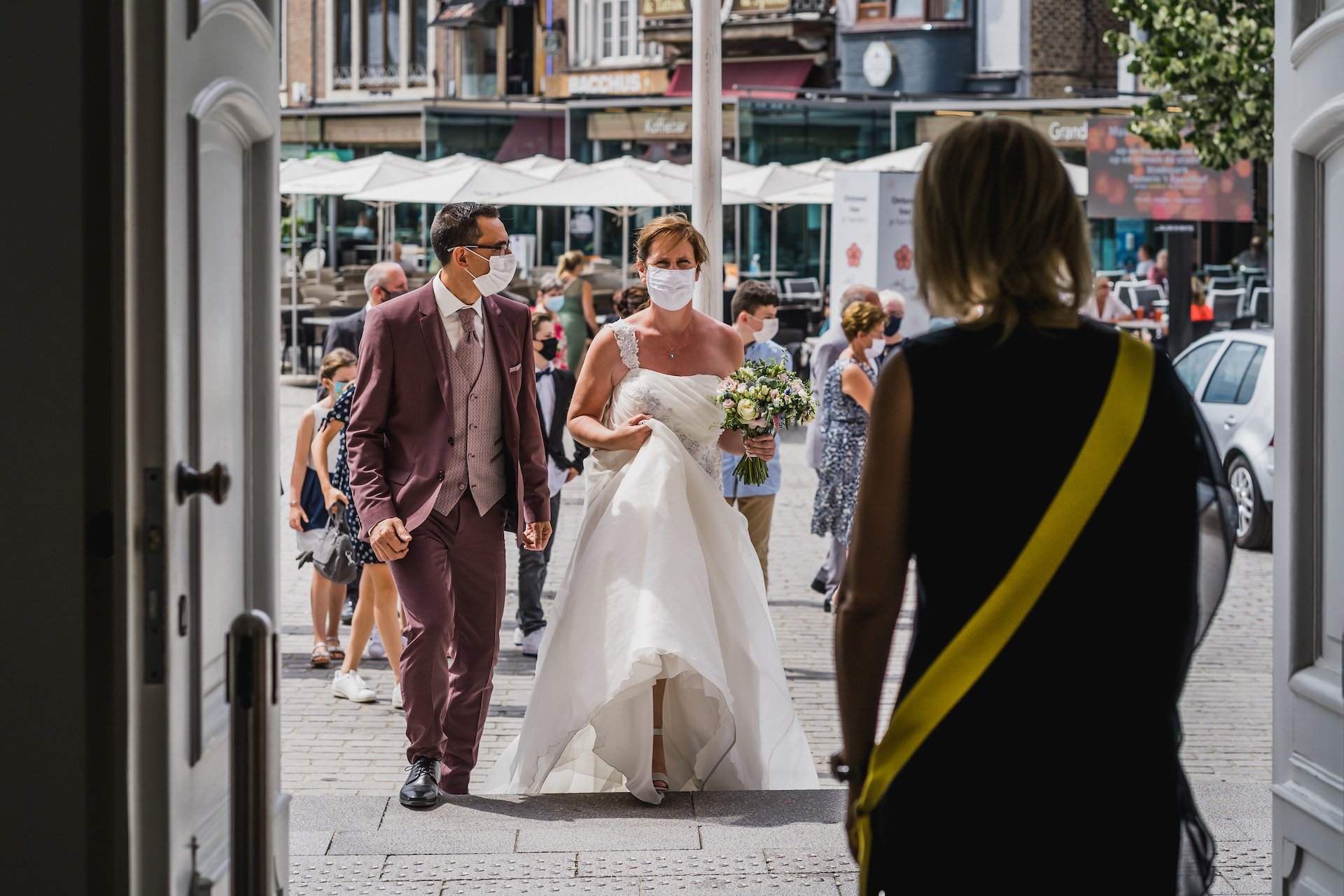 Belgian Elopement Images from the City Hall of Sint-Truiden | Wearing masks upon their arrival, the bride and groom walk into the City Hall