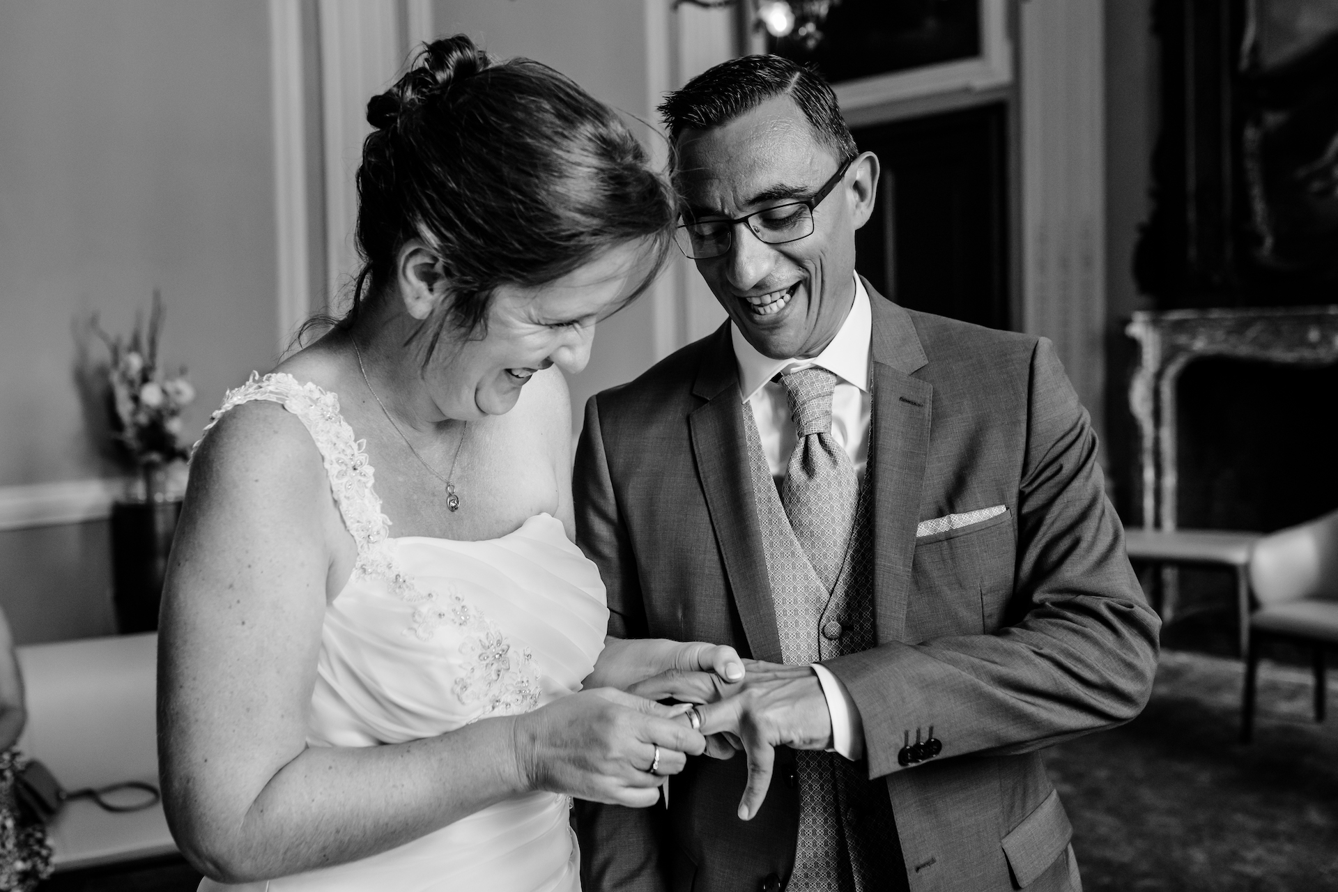 City Hall of Sint-Truiden, Brussels, Belgium Elopement Picture | The couple laugh as she tries to put his wedding ring on his finger