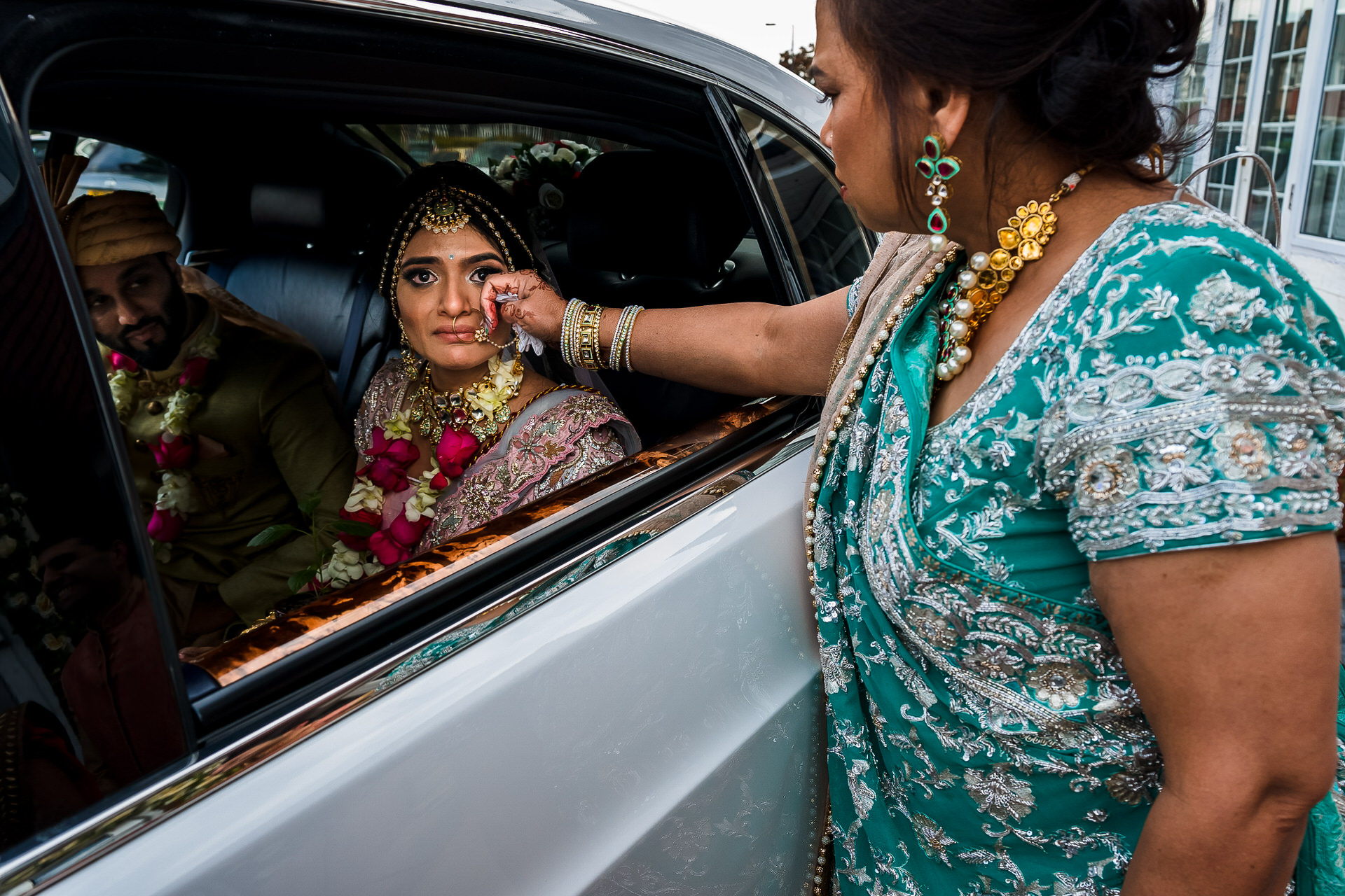 Indian Elopement Photography, London Weddings | A tear is wiped by the bride's mother as the bride prepares herself to leave
