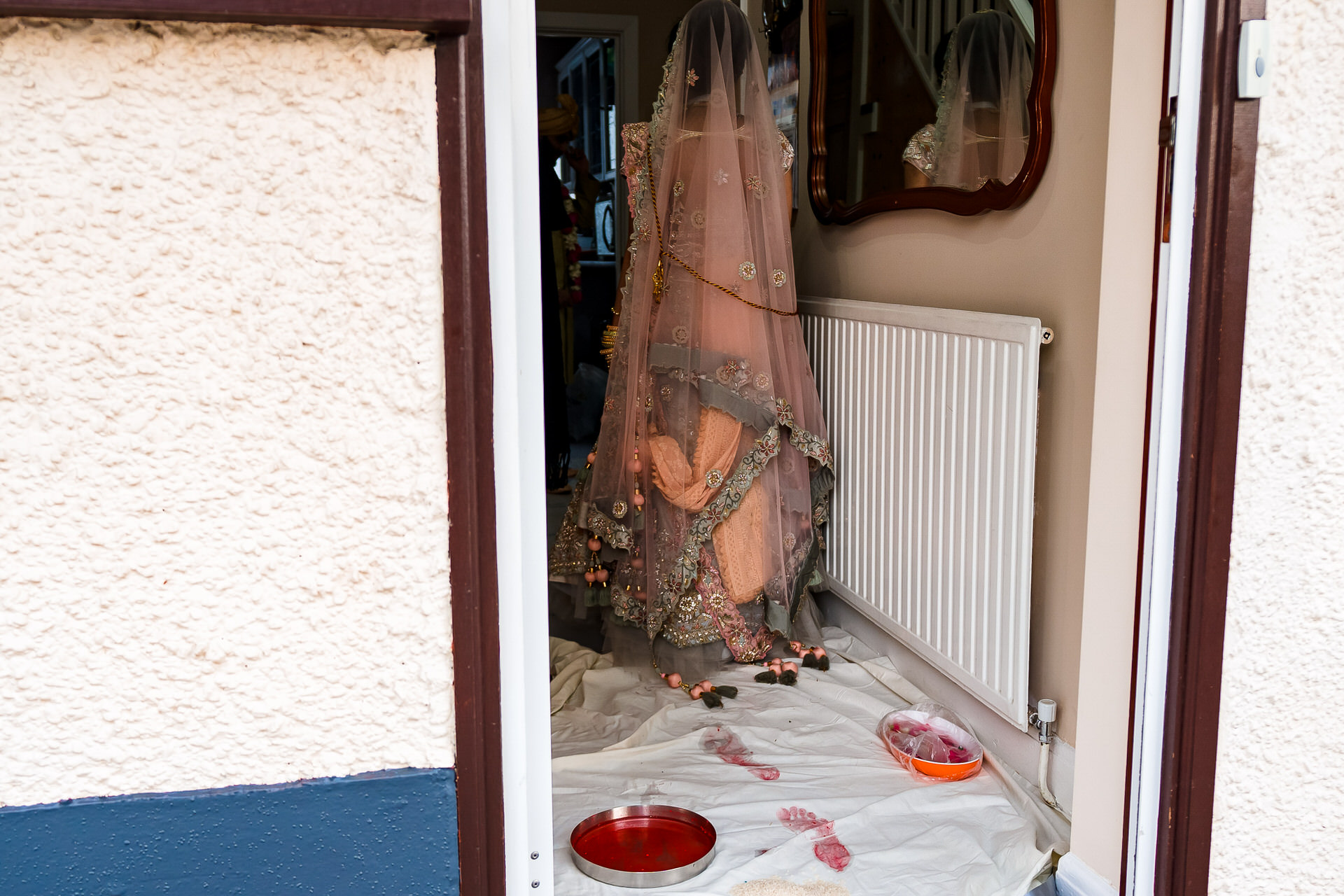 Asian Elopement Photographer for Indian Weddings UK | The bride enters her new home