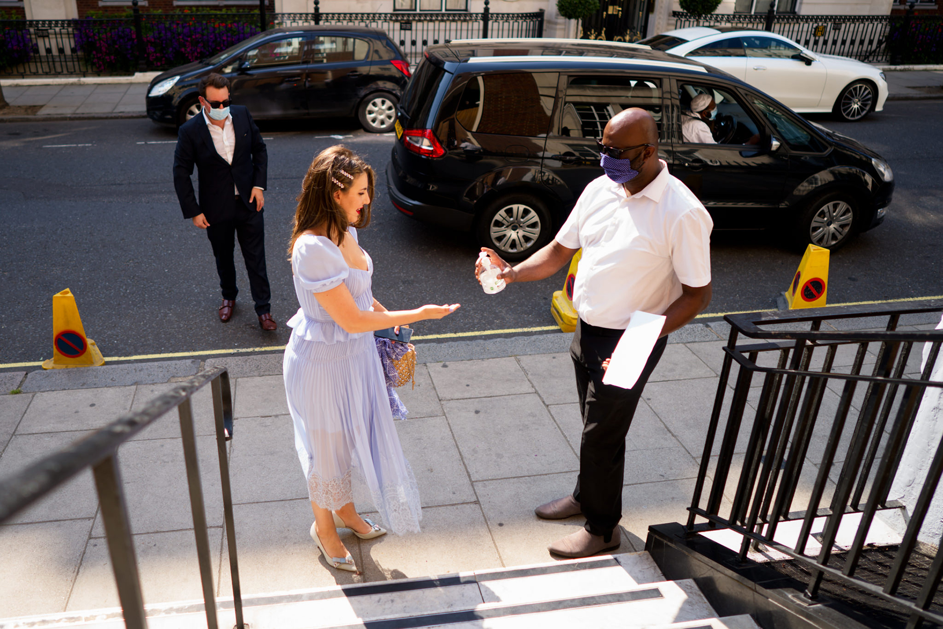 The Central Synagogue London Elopement Photos | A guest is given hand sanitizer by an attendant because of COVID