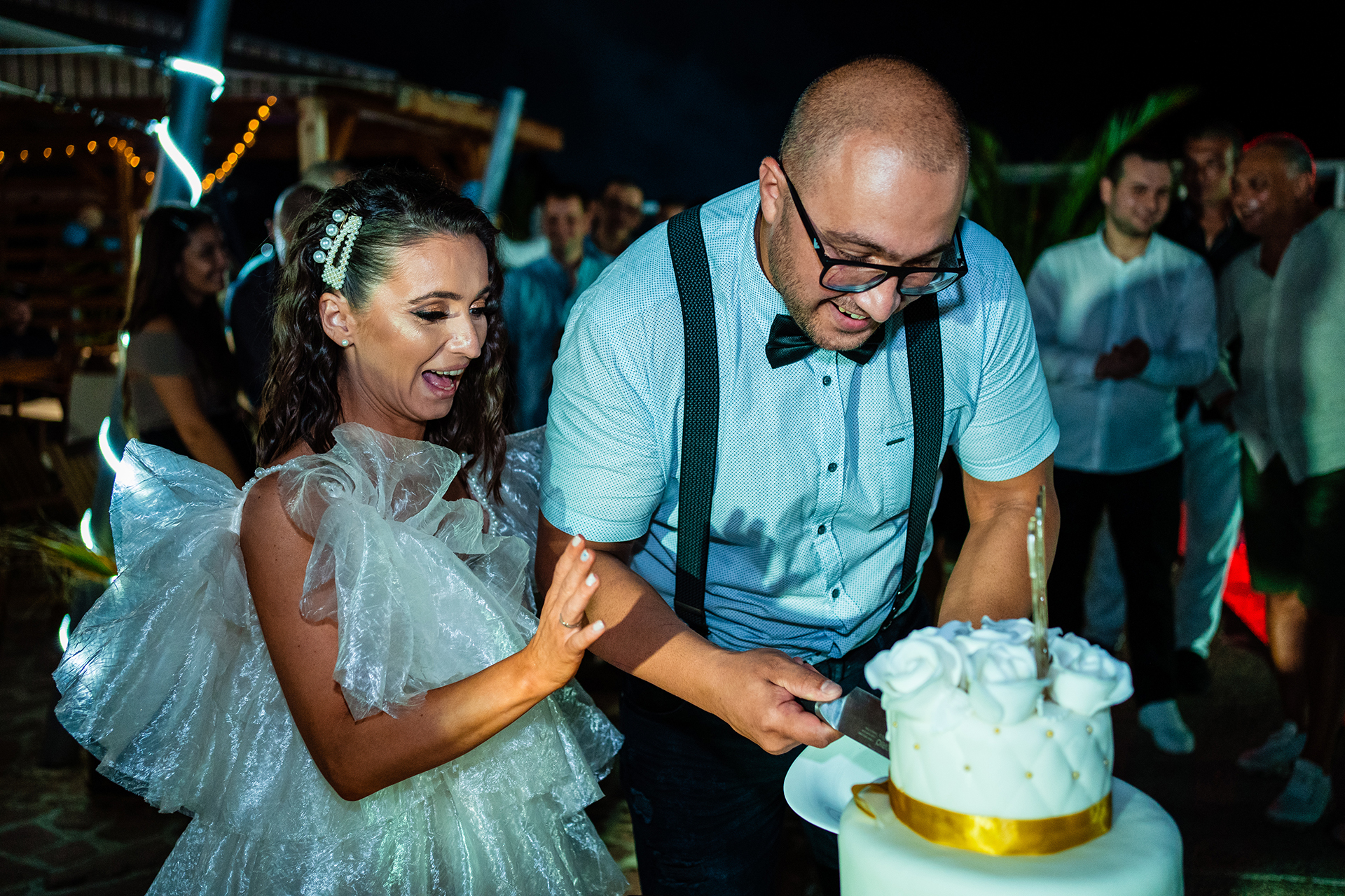 Elopement Photography from Crazy Pool, Ruse, Bulgaria | The bride watches excitedly as the groom slices the first piece of cake