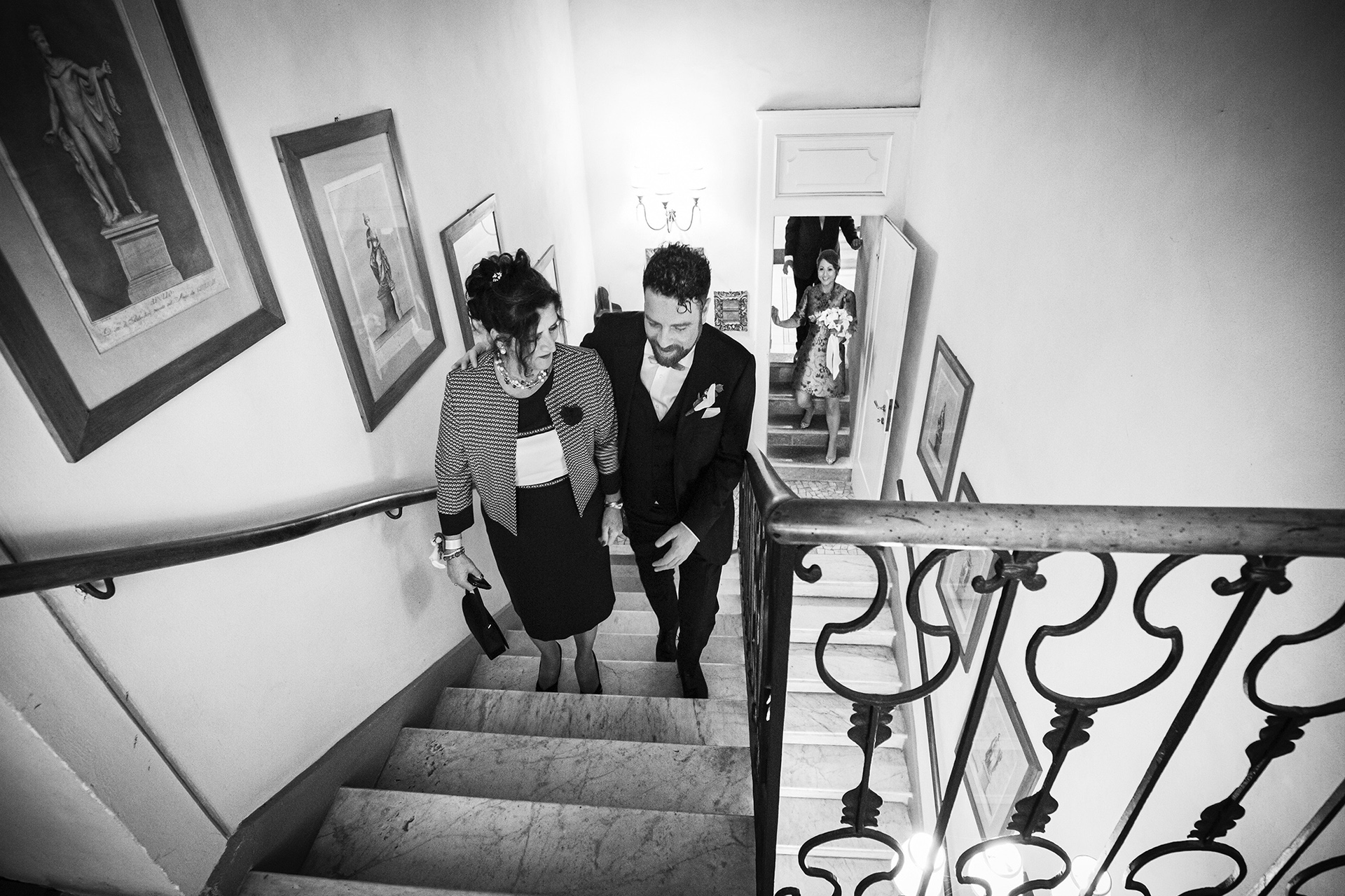 Villa Bossi, Varese - IT Elopement Photographer | The groom helps his mother walk up a marble staircase