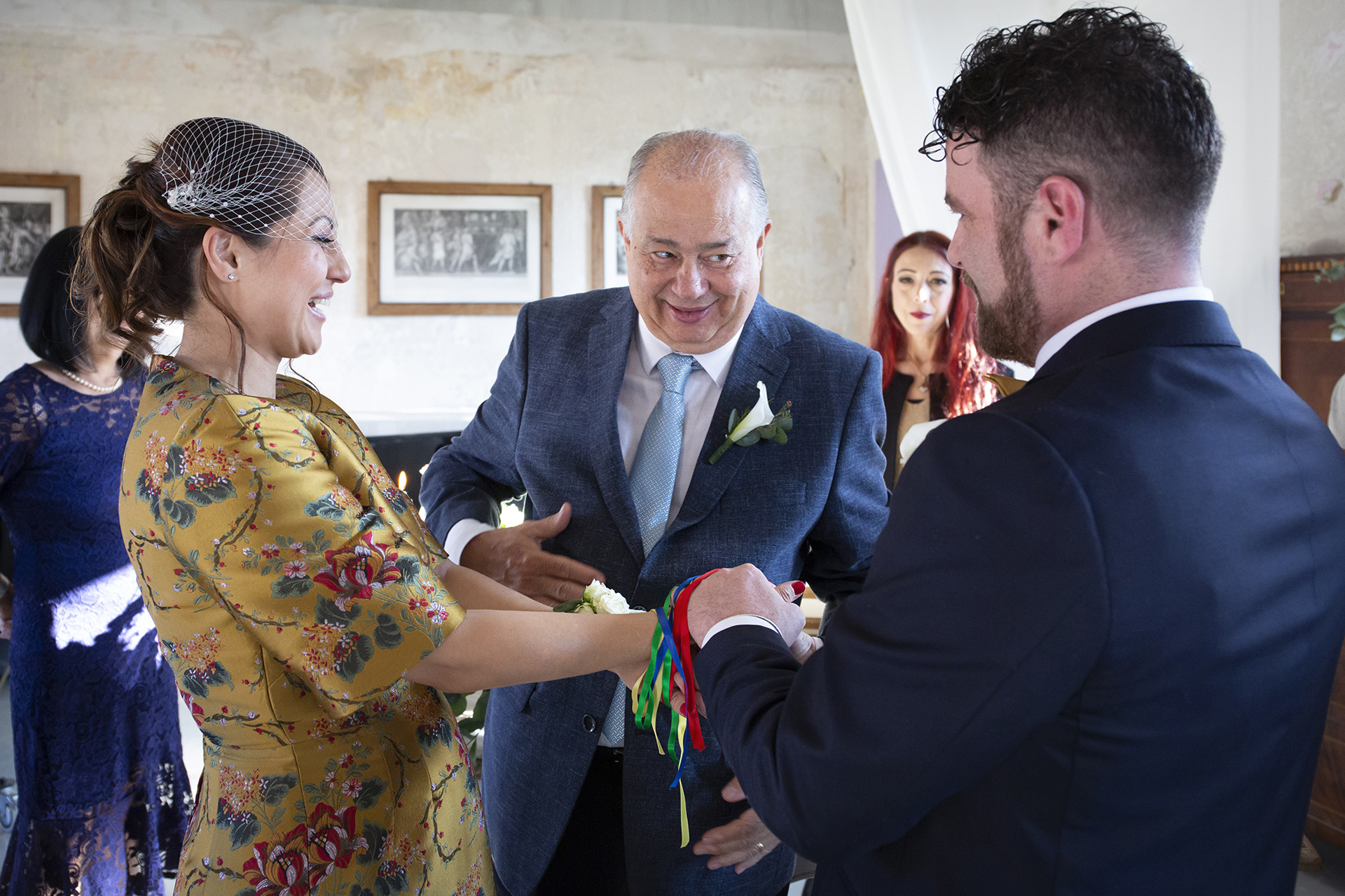 Villa Bossi Legal Civil Ceremony - Lake Varese Elopement Photo | The bride's father performs a special blessing by wrapping ribbon around the couple's wrists