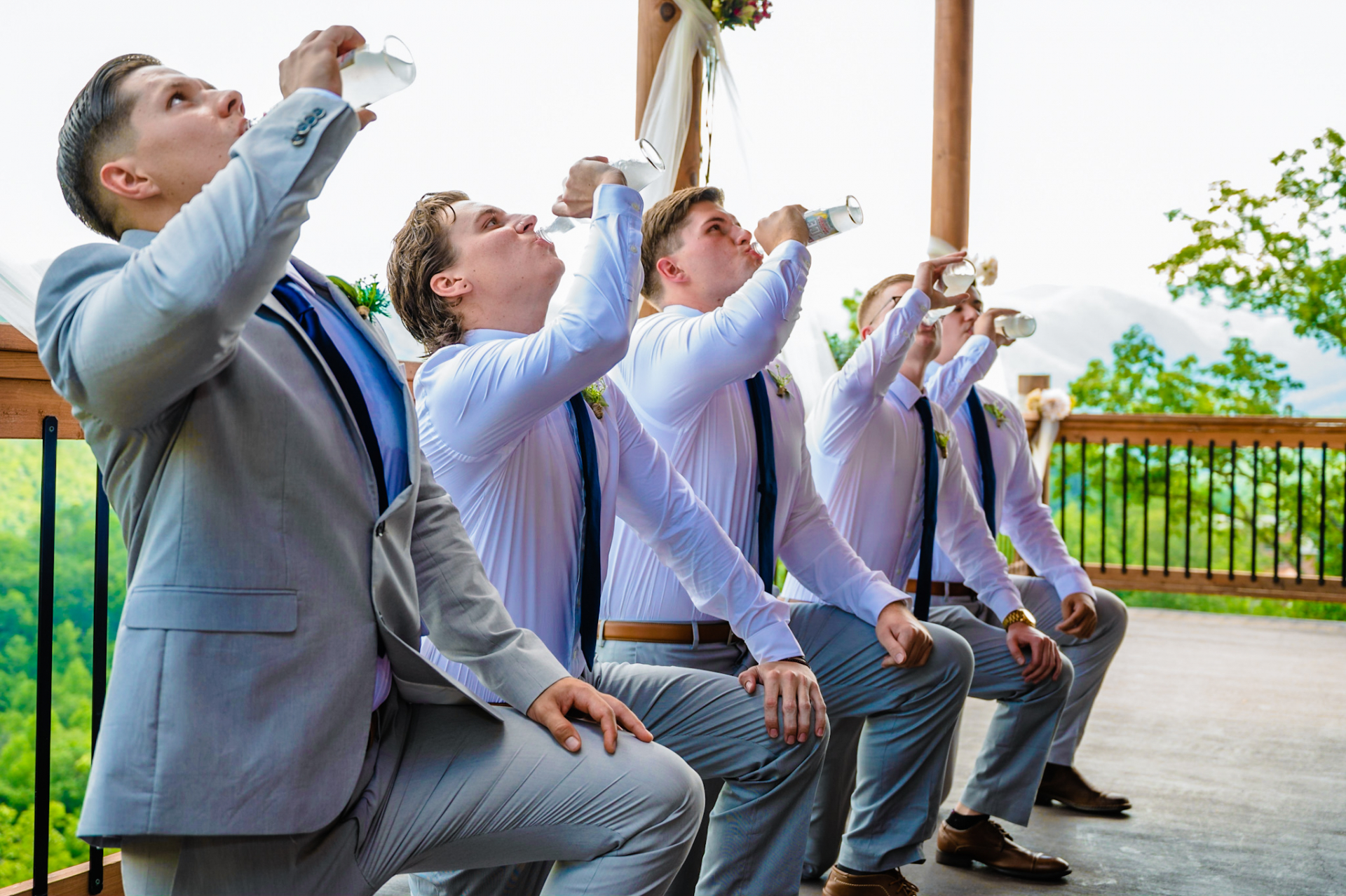 Pigeon Forge - Timber Top Cabins Elopement Venue | the groom and groomsmen got on one knee to drink the entire bottle