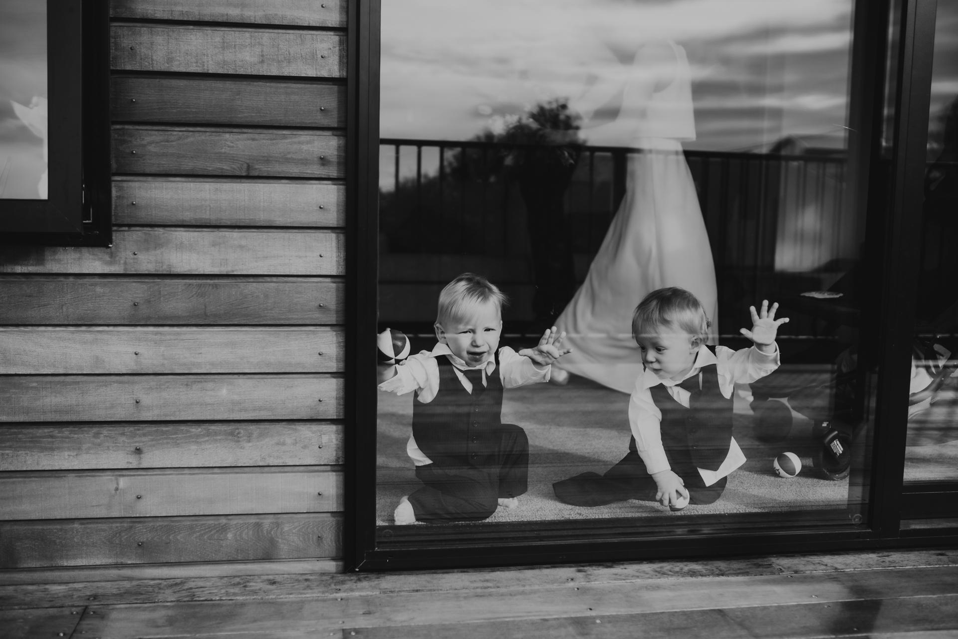 Fotograaf schaking in Nieuw-Zeeland | twee kleine jongens die zich amuseren en door de grote schuifdeur naar het balkon kijken