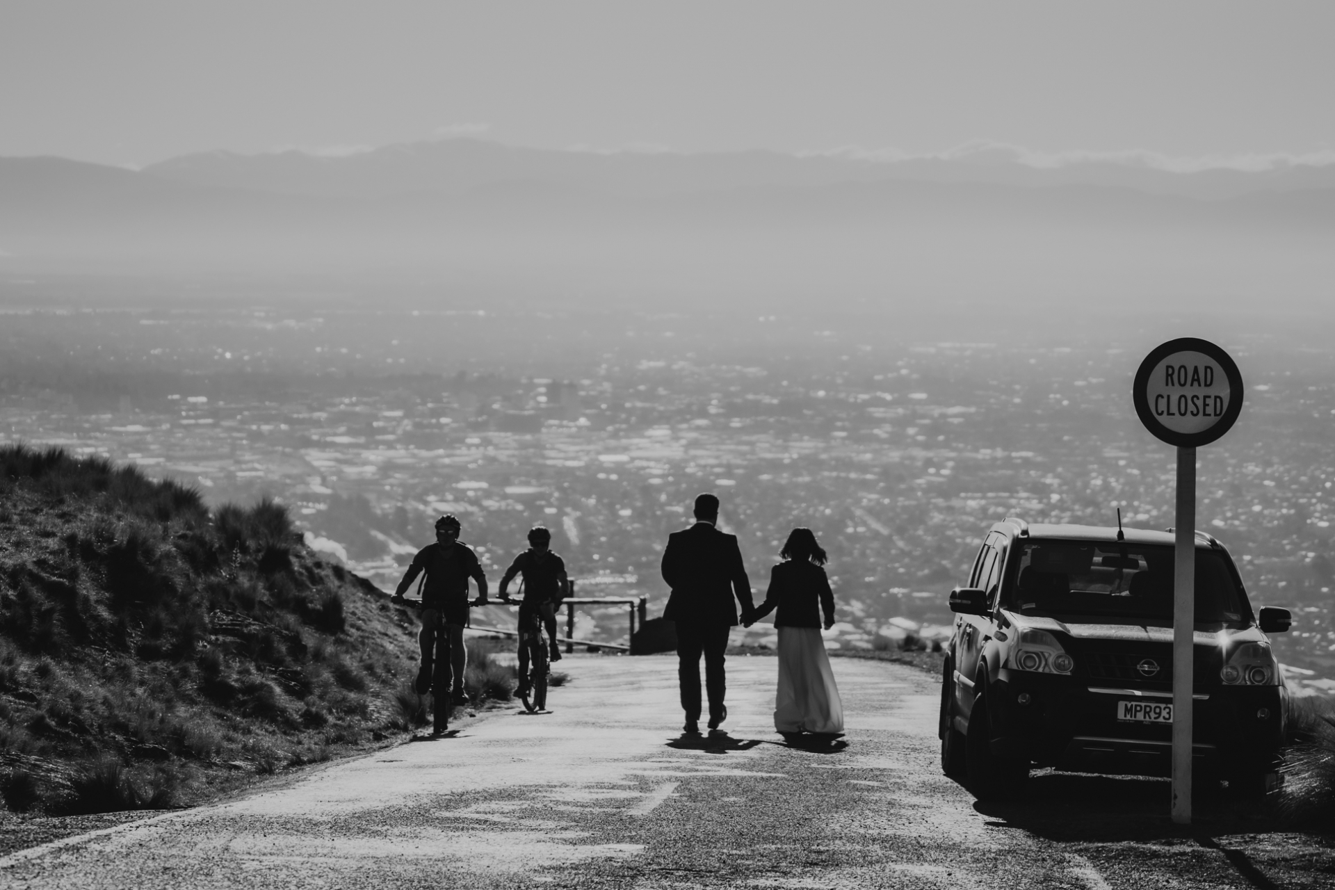 Port Hills, Christchurch Nieuw-Zeeland Elopement Foto | De bruid en bruidegom lopen terwijl ze omringd zijn door het glanzende water van de haven