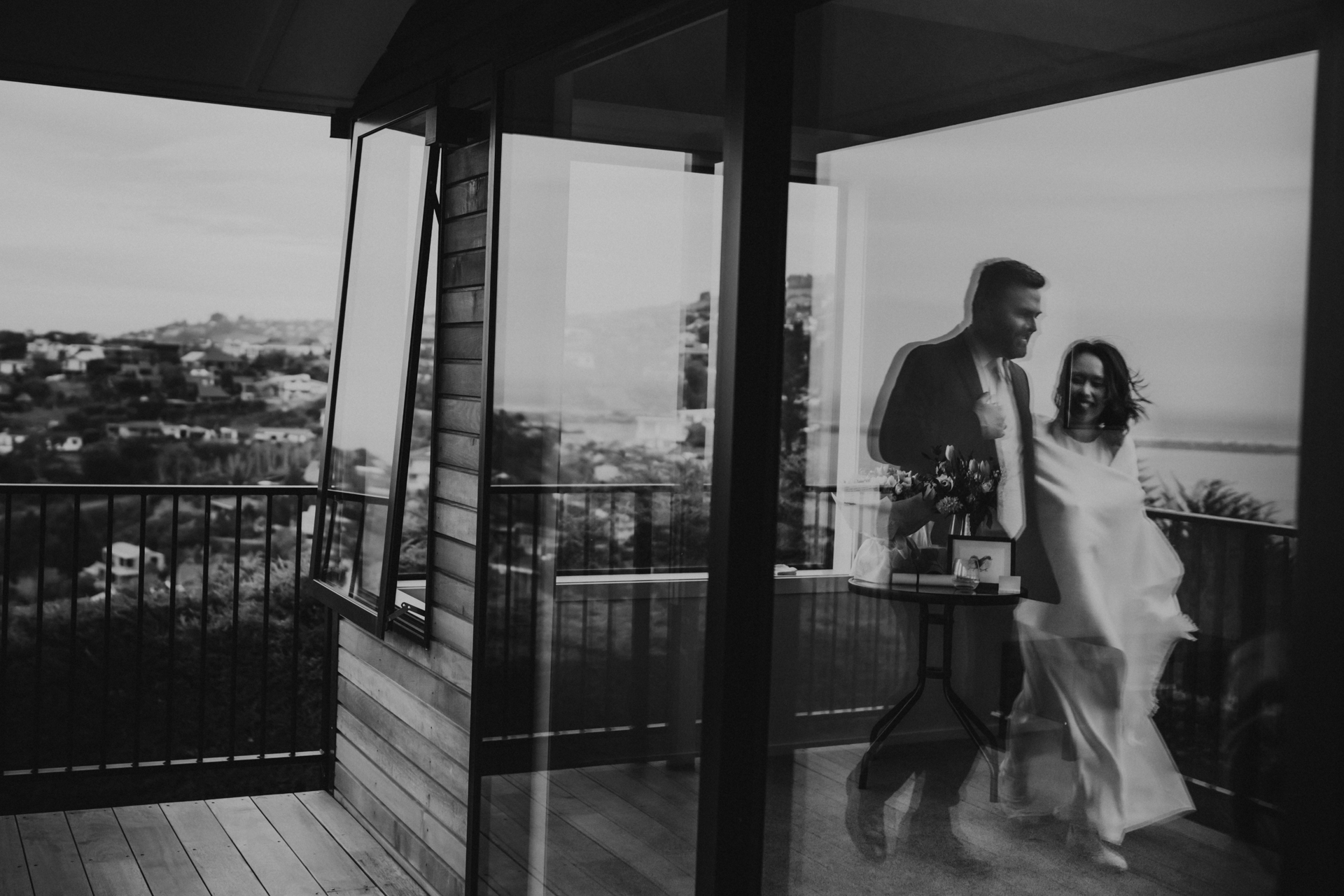 Christchruch Elopement Ceremony Picture | the couple, now happily married and smiling, reflected in the large balcony window