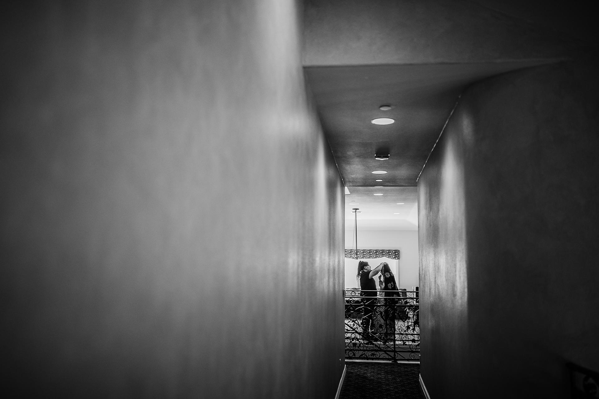 Elopement-fotografen voor Pleasanton, Californië | Aan het einde van een lange gang helpt een vrouw de bruid met wat op het laatste moment bijwerken