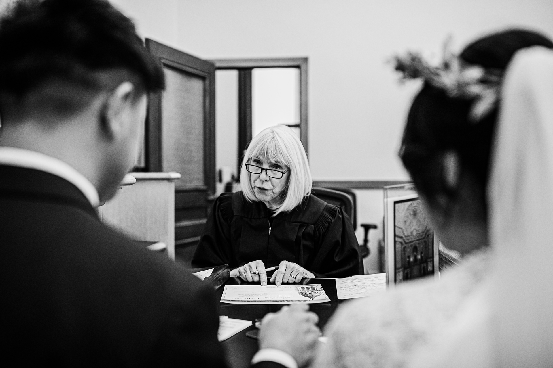 SF City Hall Wedding Photographer for San Francisco, CA | The bride and groom sit at the judge's desk holding hands