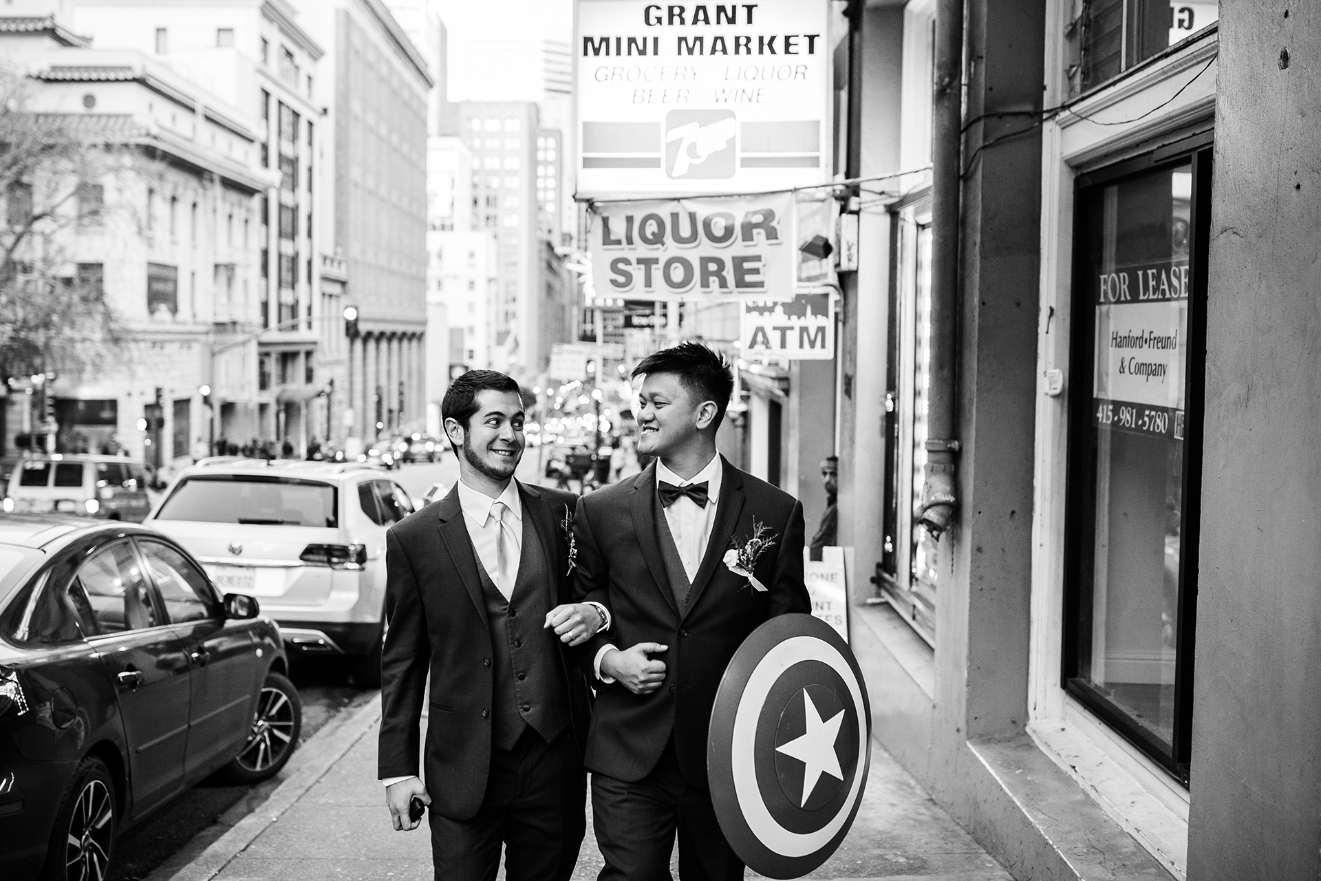 San Francisco City Hall Wedding w/ Portraits in Chinatown | After the ceremony, the best man and the groom, who's carrying a Captain America shield, goof off with one another