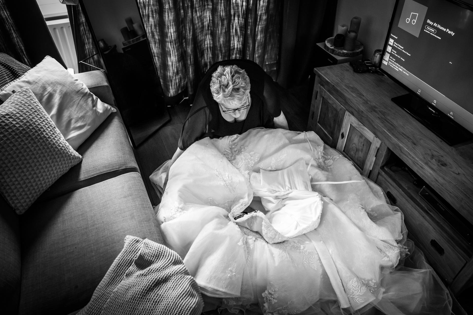 Breda, Paesi Bassi Elopement Photographer | La madre della sposa posa l'abito in soggiorno