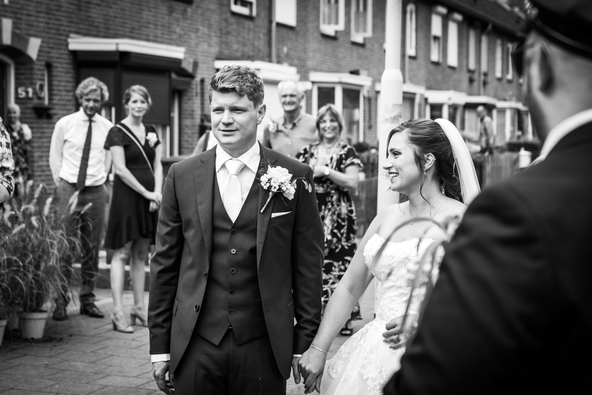 Breda, NL Elopement Pictures | In front of the house of the bride and groom, the family is watching the couple