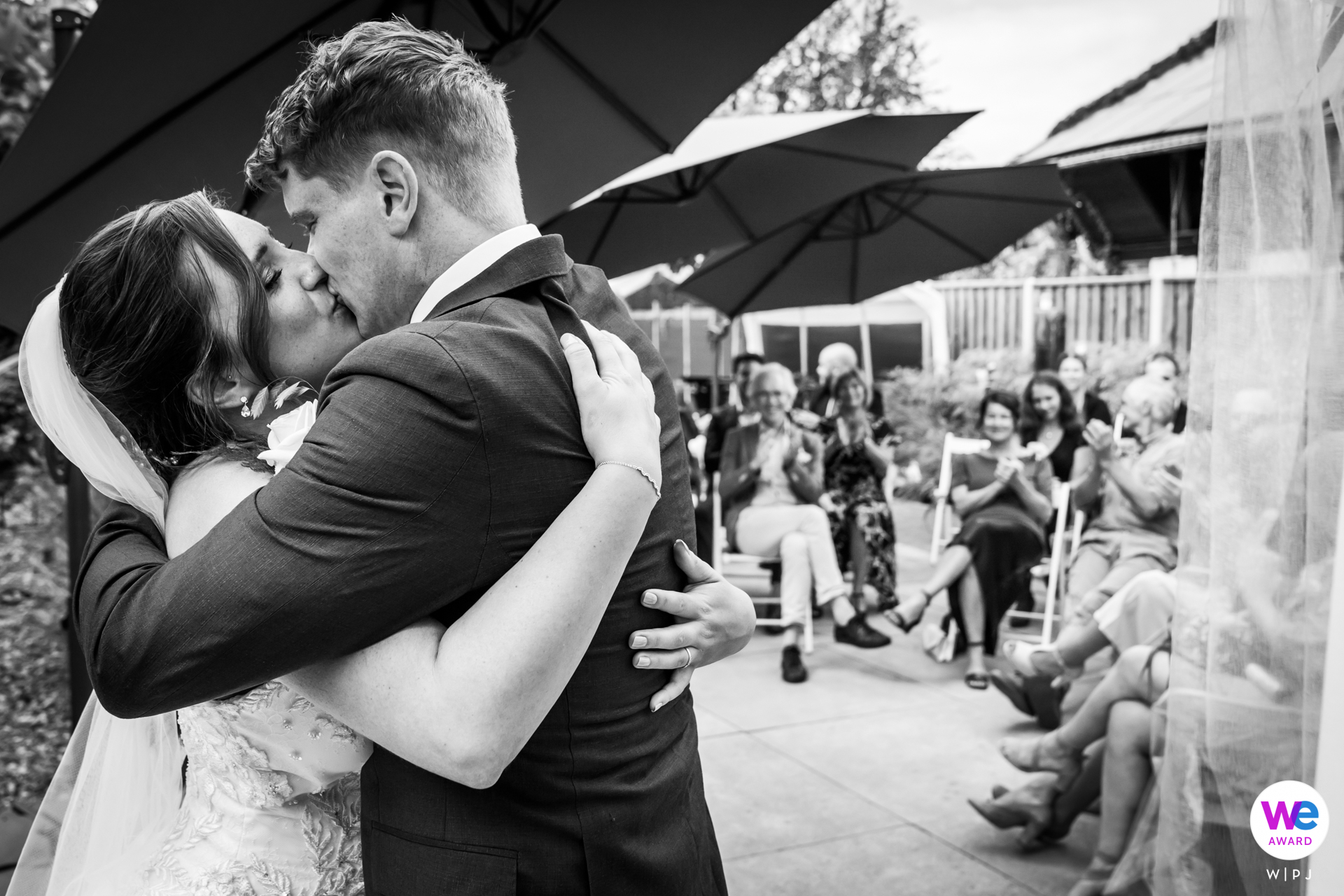 Restaurant Pouwe, Hoeven Garden Elopement Venue Photos | An intimate kiss of the bridal couple, as the guests watch