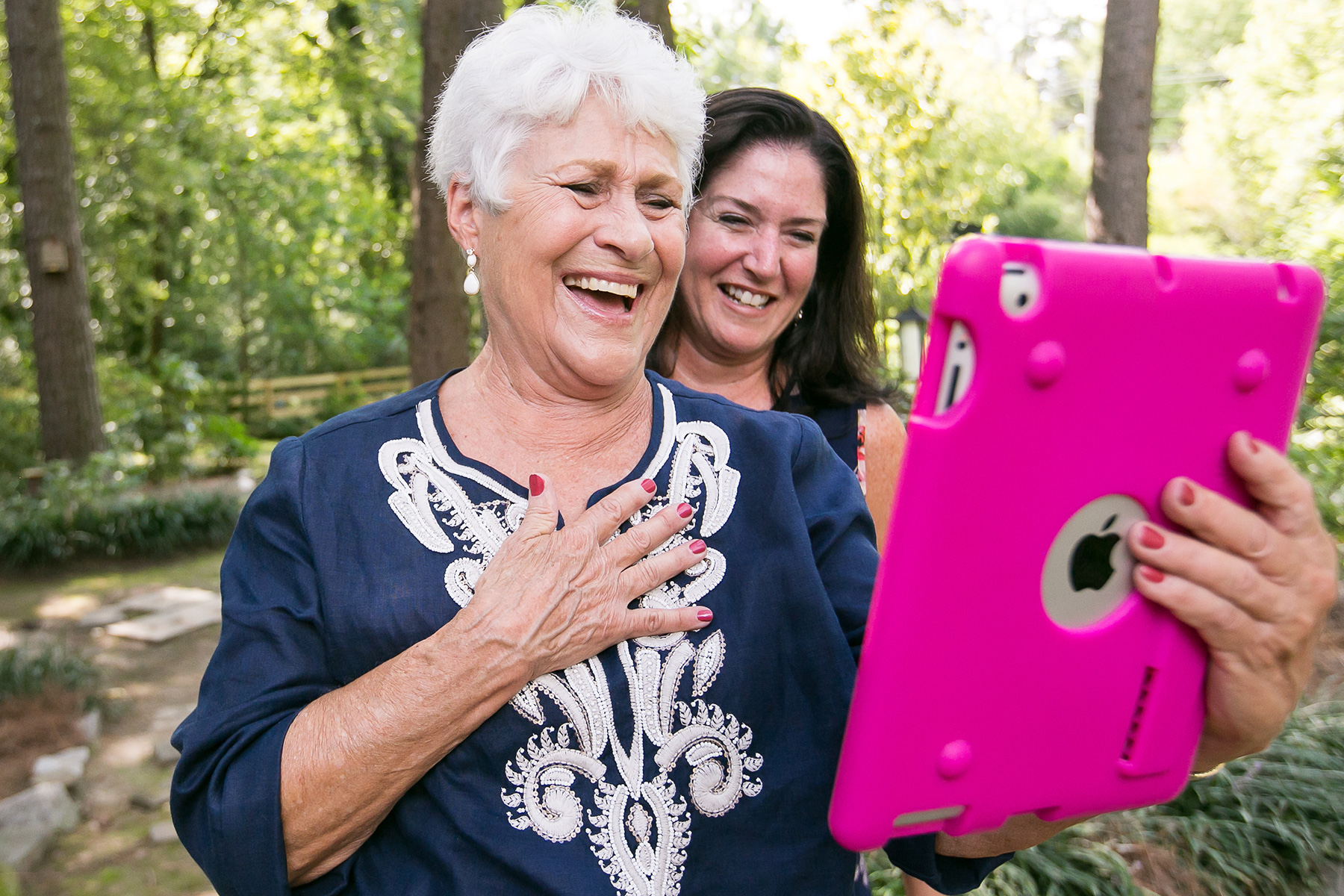 Backyard Wedding Photography | Mom and sister laugh with family who zoomed in from Australia