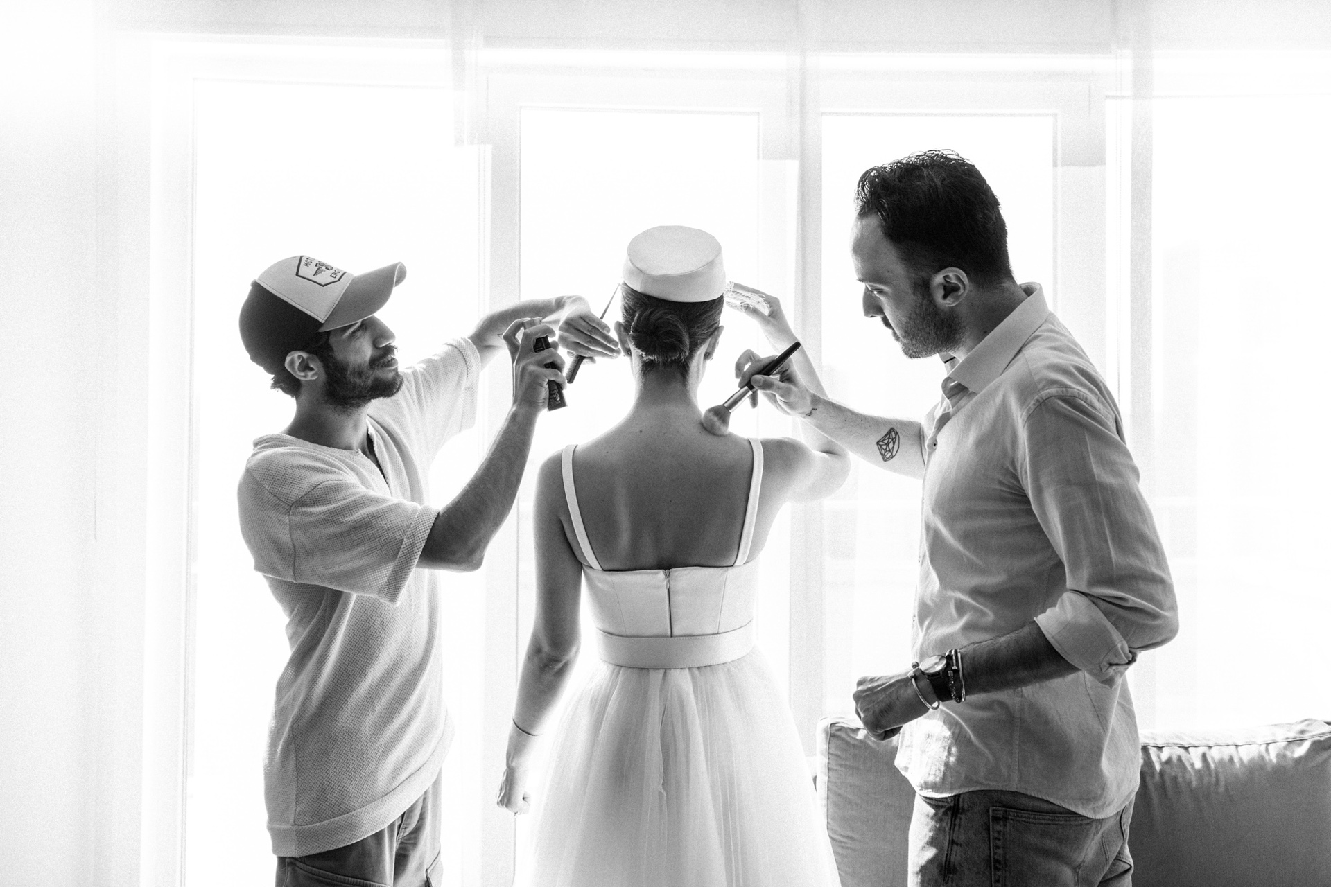 Istanbul Backyard Elopement Image | Two men help put the finishing touches on the bride's hair and makeup