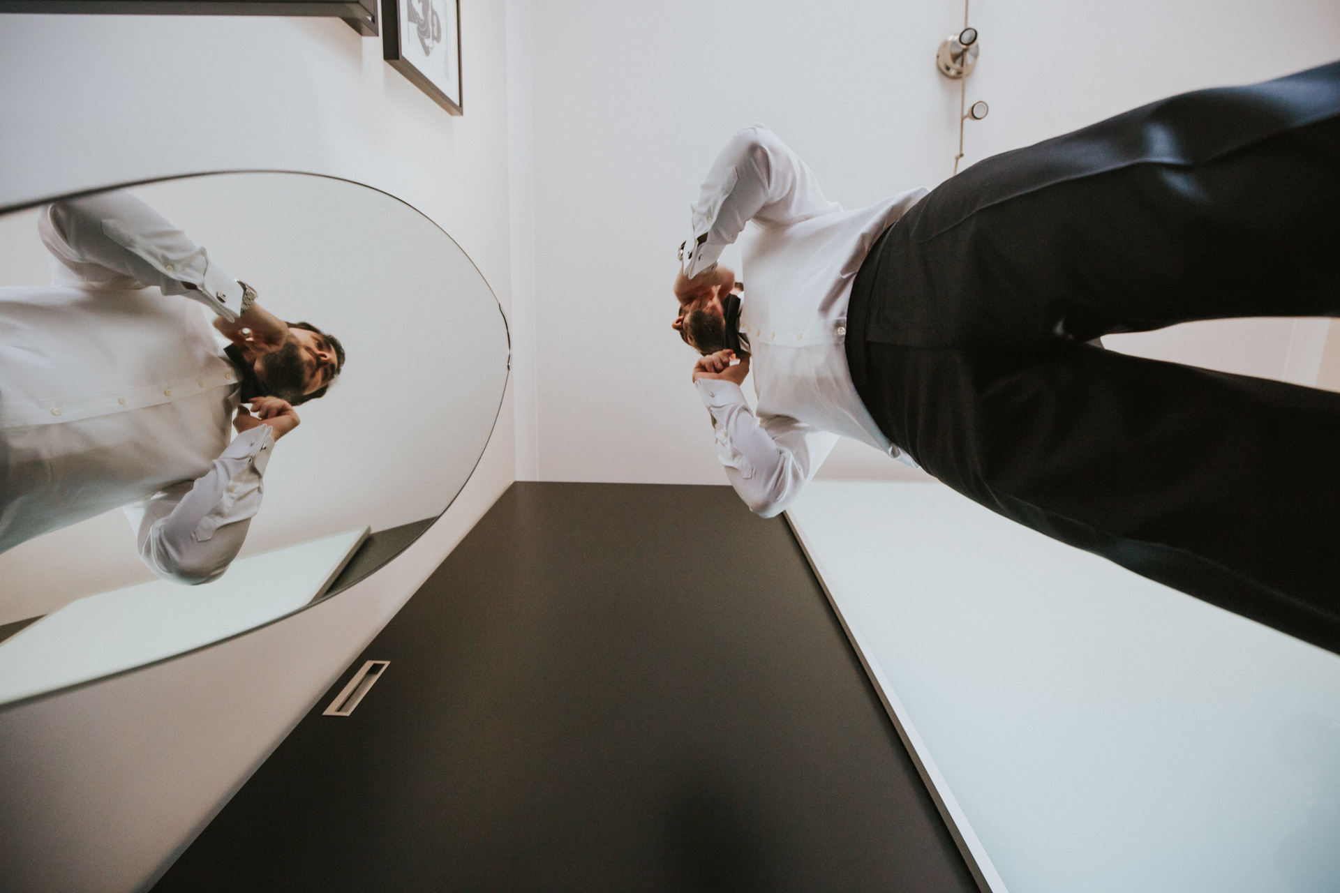 Turkey Elopement Photos | Seen from below, the groom adjusts his bowtie in the mirror