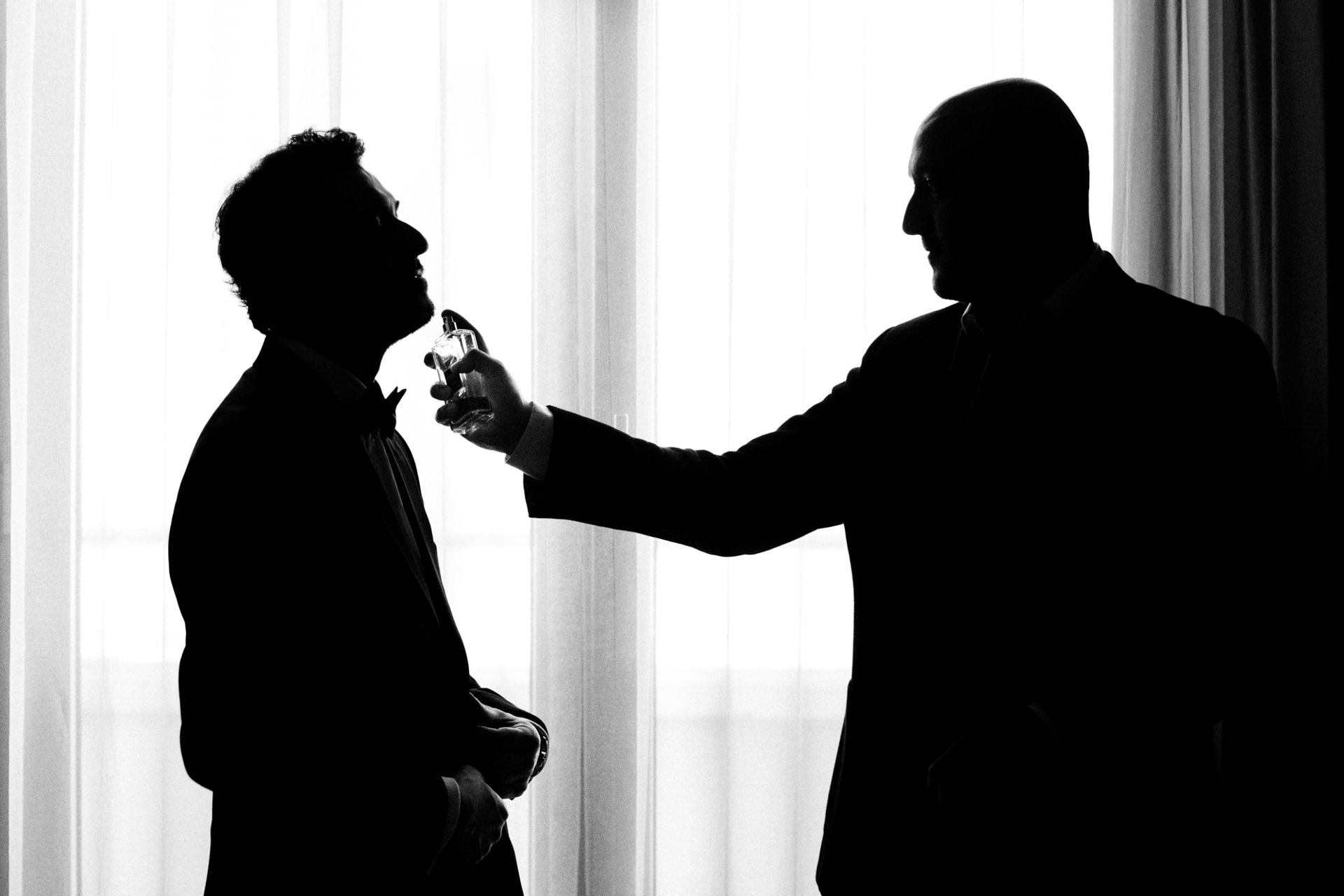 Istanbul Pre-Ceremony Elopement Prep Photo | Standing in front of a bright window, we can see the silhouette of the best man and the groom