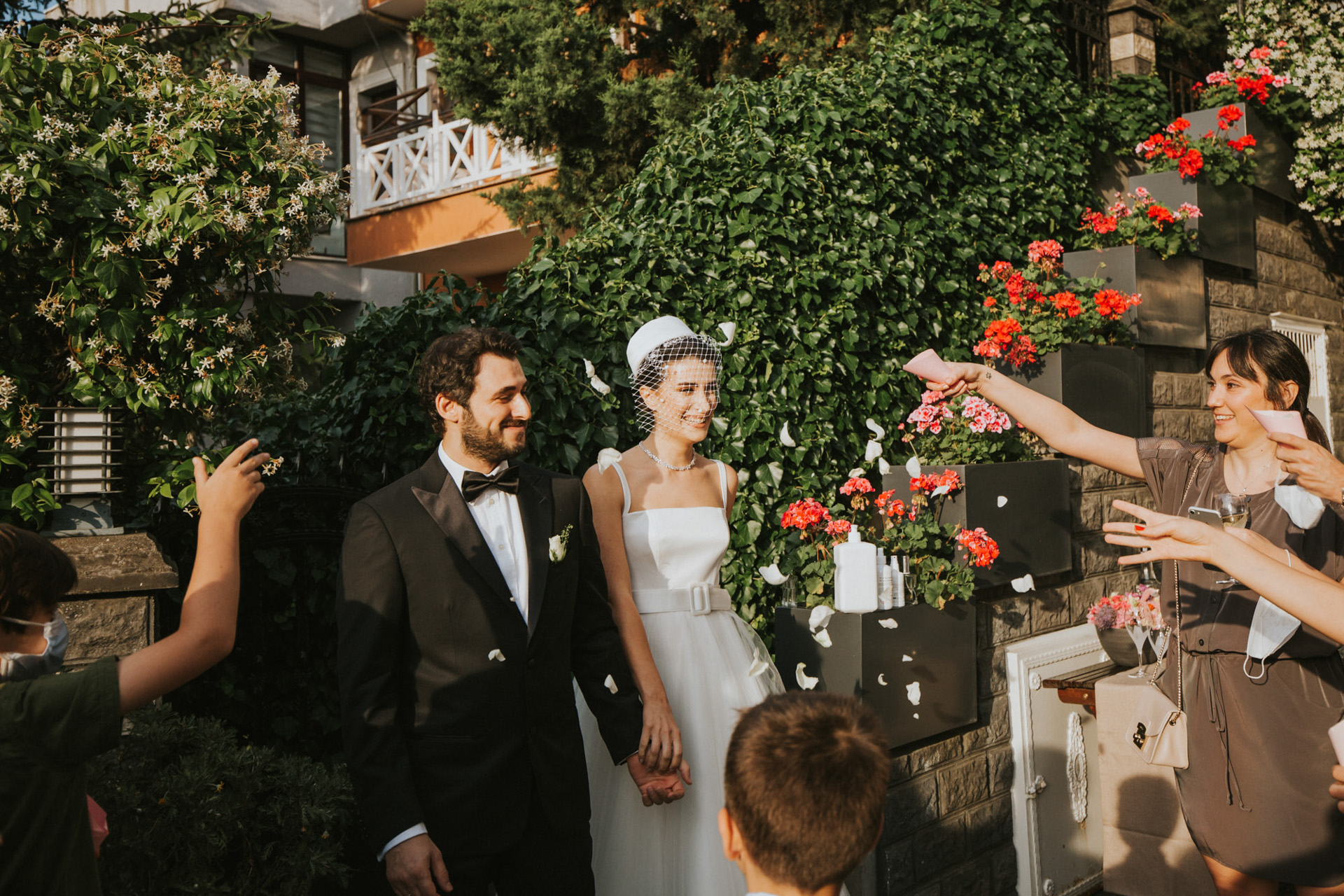 DIY Intimate Backyard Wedding Photos from Istanbul | the newlyweds leave the ceremony, holding hands and walking past the lush greenery