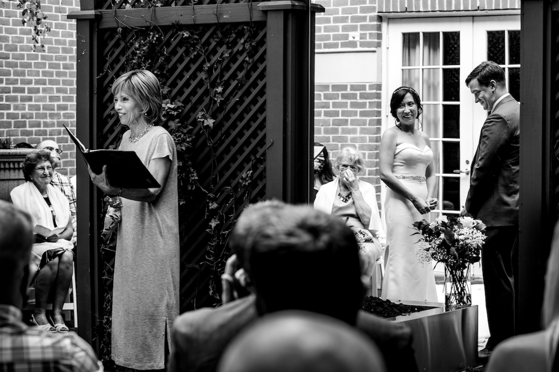 Alexandria, VA Outdoor Elopement Venue Images | the officiant reads aloud, momentarily separated from the couple by a large, vine-covered trellis