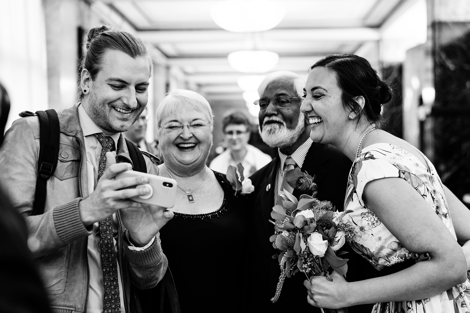New York City Hall Elopement and Wedding Images | The bride and her guests look with delight at snapshots