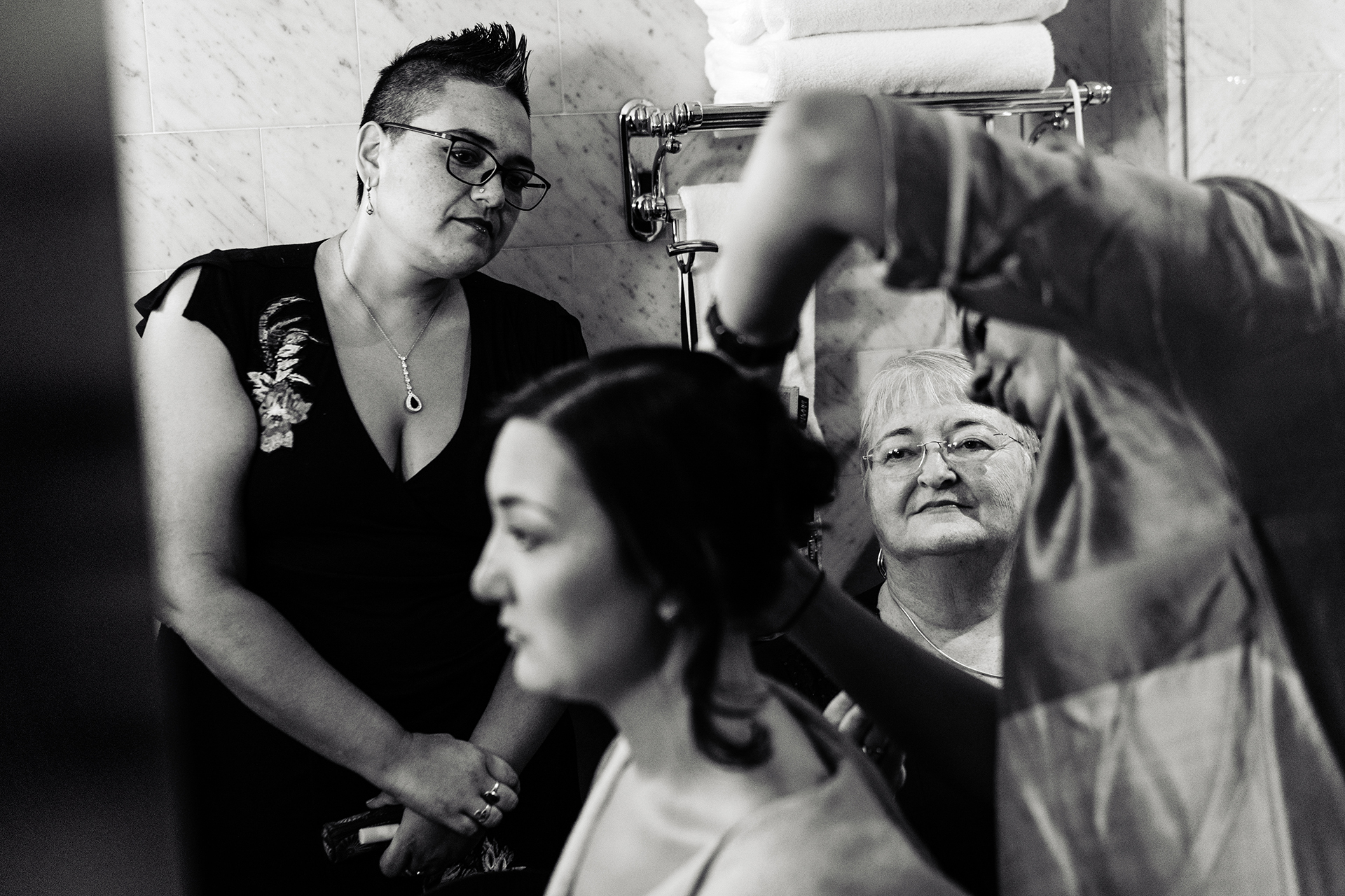NYC Elopement Photography | The bride's mom and sister look on as she gets ready